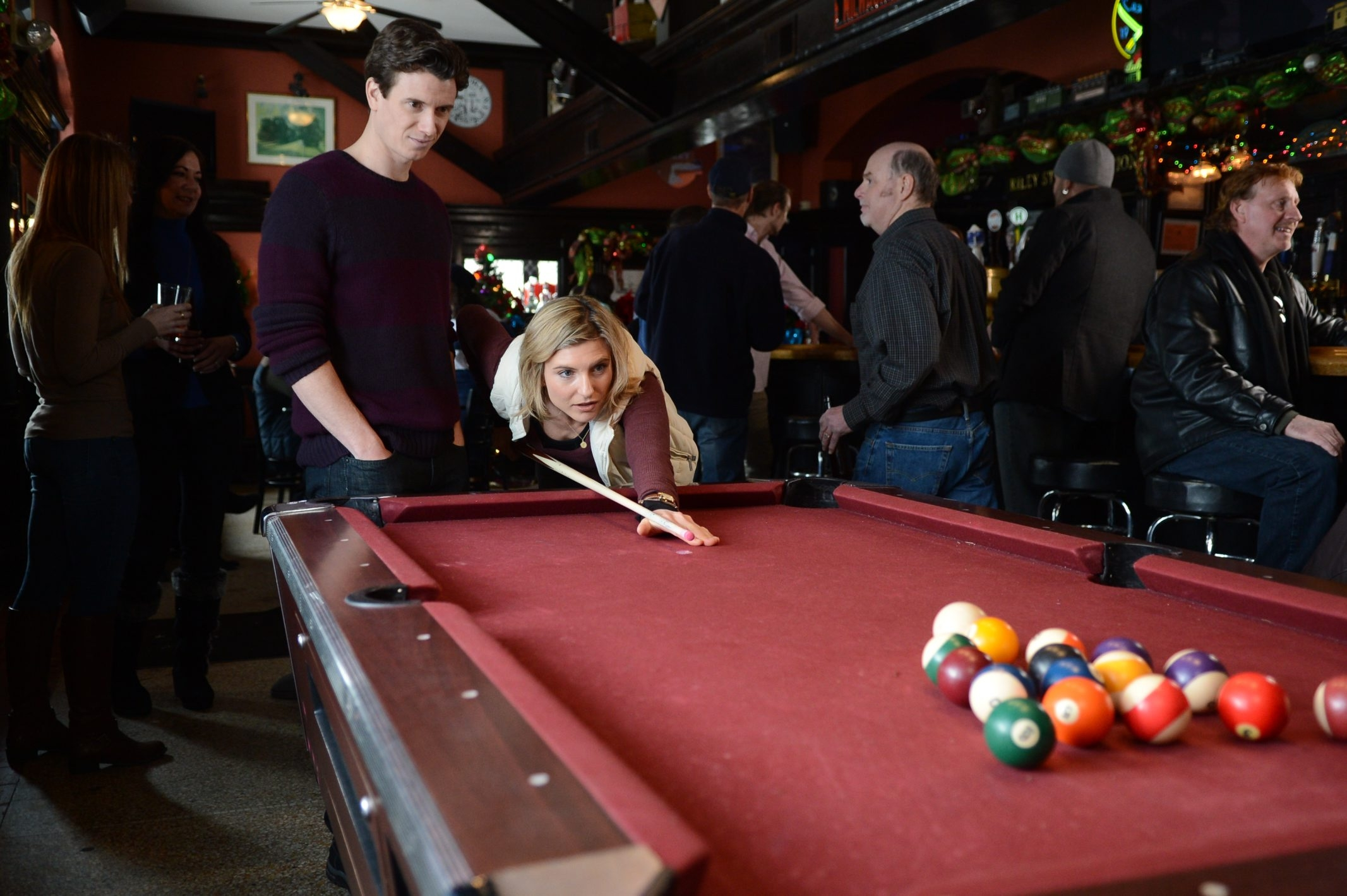 """In this scene from """"A Prince for Christmas,"""" stars Kirk Barker and Viva Bianca are shooting pool in Riley Street Station in East Aurora."""