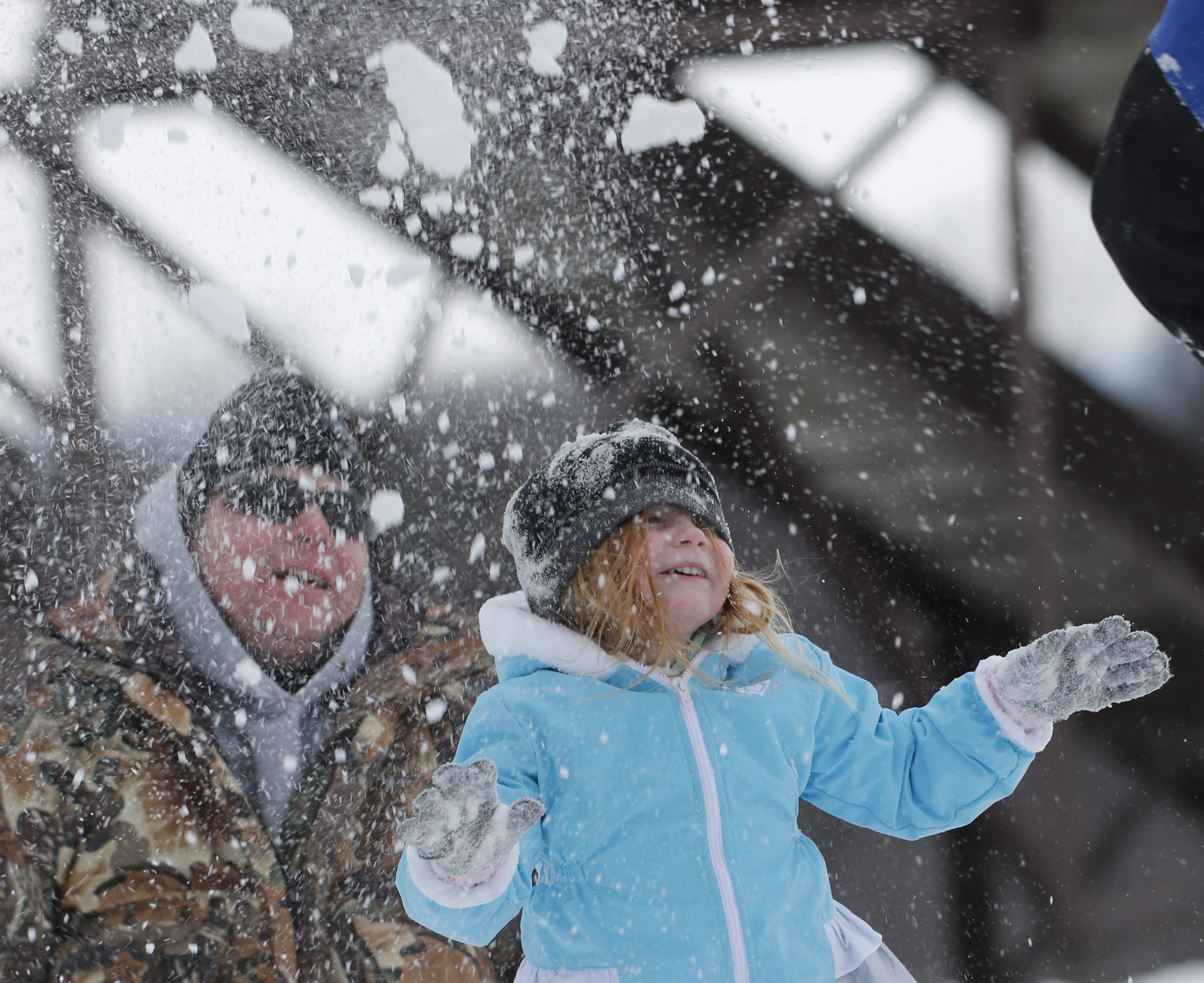 Mike Bogue of West Seneca tosses snow in the air over his 5-year-old niece Bailey Bogue of St. Augustine, Fla., who was playing in the snow for the first time in her life at Chestnut Ridge Park in Orchard Park, Saturday, Dec. 19, 2015.