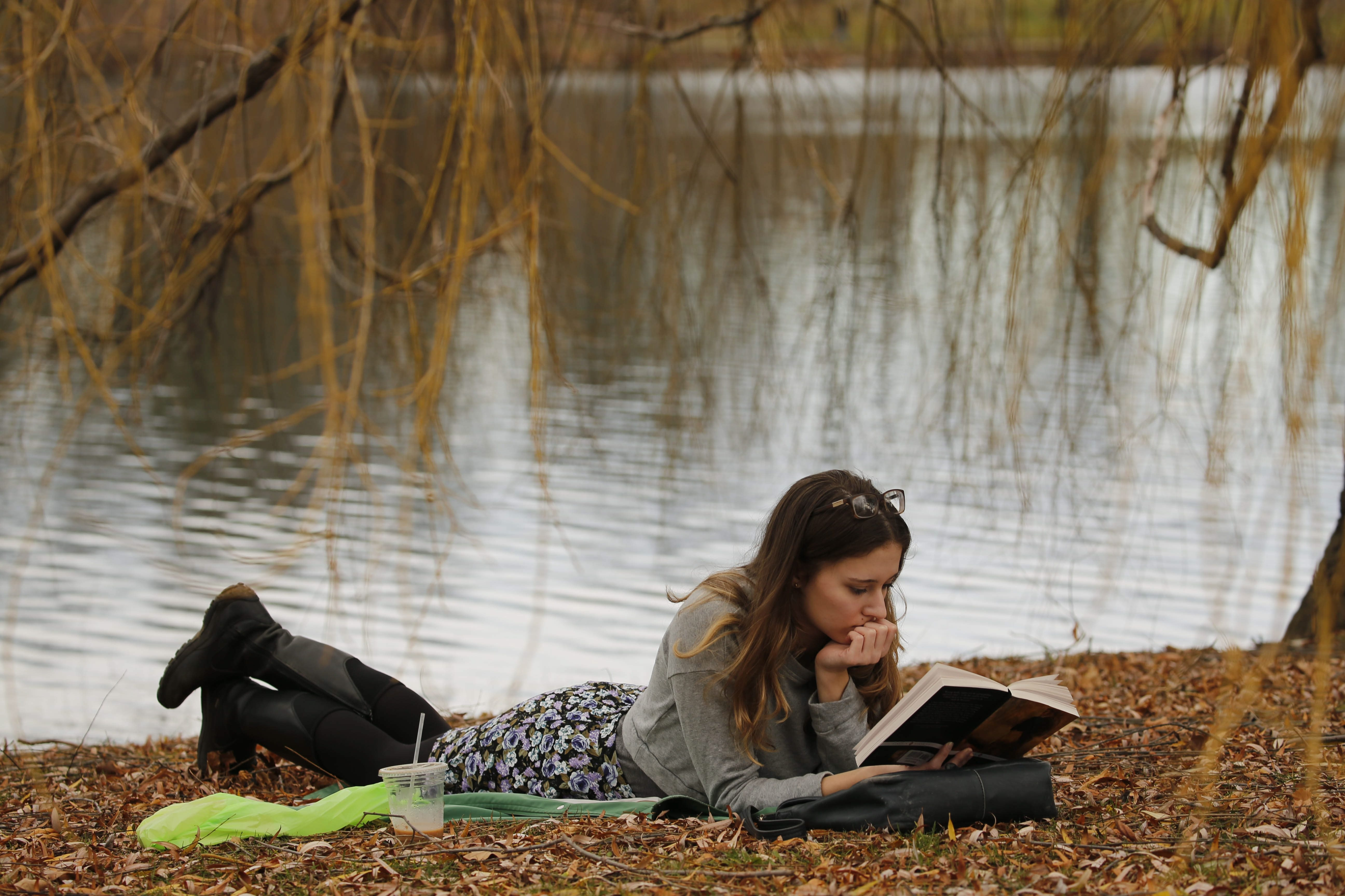 Grace Philips, of Buffalo, relaxes with a book at Hoyt Lake on a day when temperature here hit 70 in December for only third time ever.