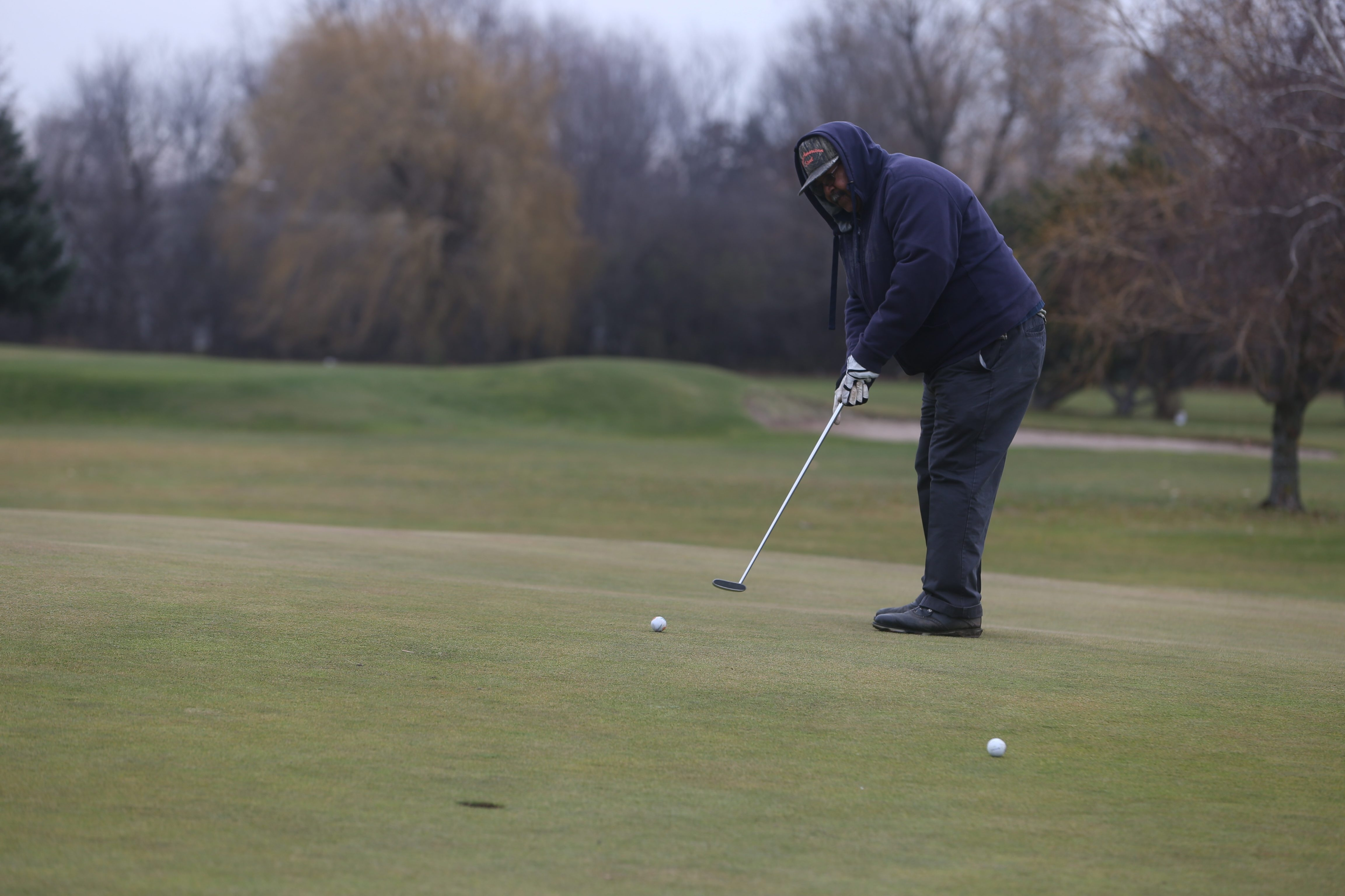Golfers such as Carl Smith, shown here putting on the 15th hole at Grover Cleveland Golf Course on Dec. 10, are taking advantage of the warm weather and clear skies to get back out on the course.