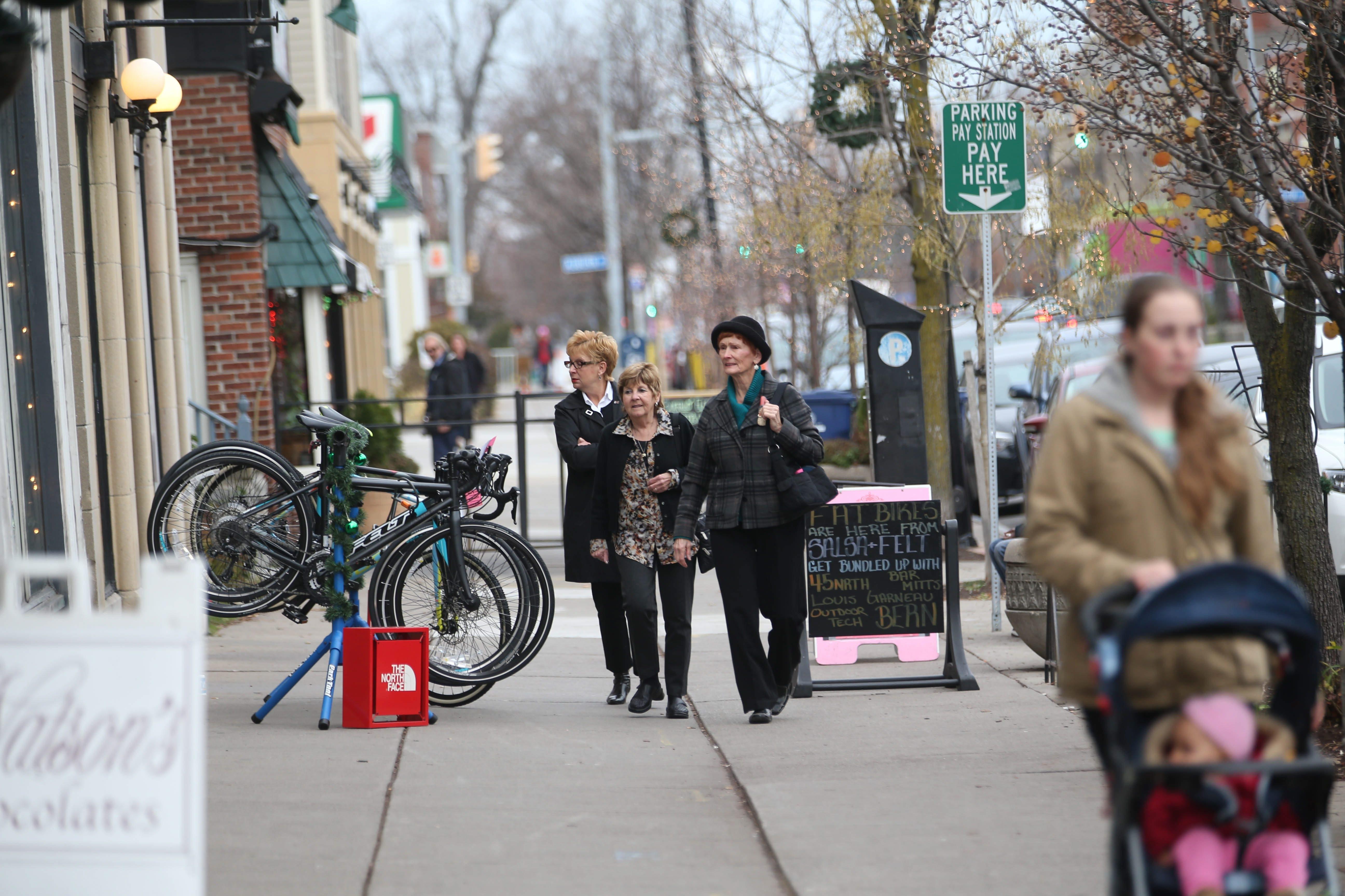 Christina Pokoj, left, of Orchard Park; Dale Nikitas, of Barker; and Jan Adair, of Lockport, walk toward Everything Elmwood on Dec. 10. (Sharon Cantillon/Buffalo News)
