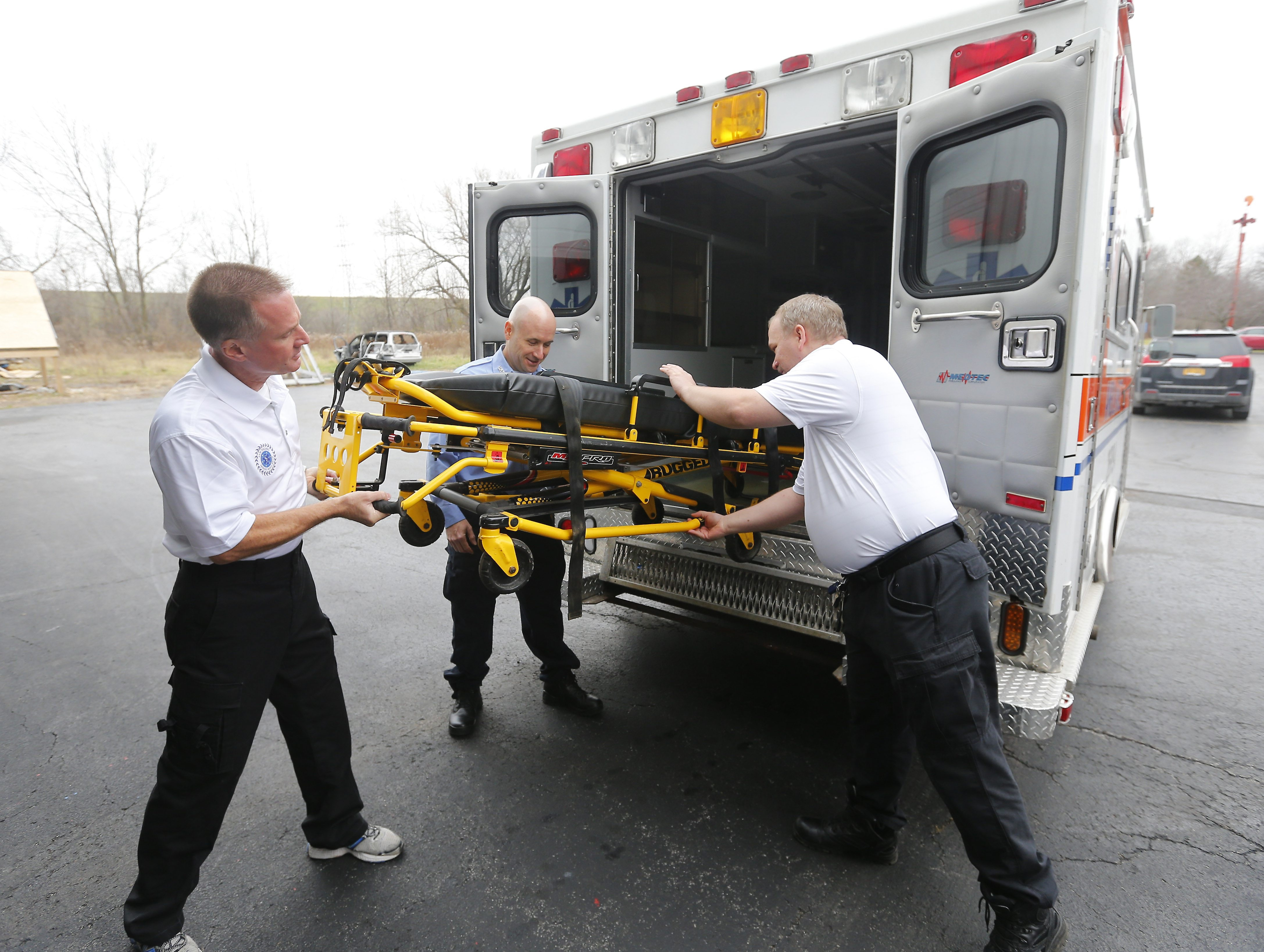 From left, Alex Parmelee, Greg Sitek and Dominick Walenczak load an ambulance with donated medical supplies for its trip to San Pedro, Belize. The Upper Mountain Fire Company is donating the ambulance and equipment to the impoverished town.