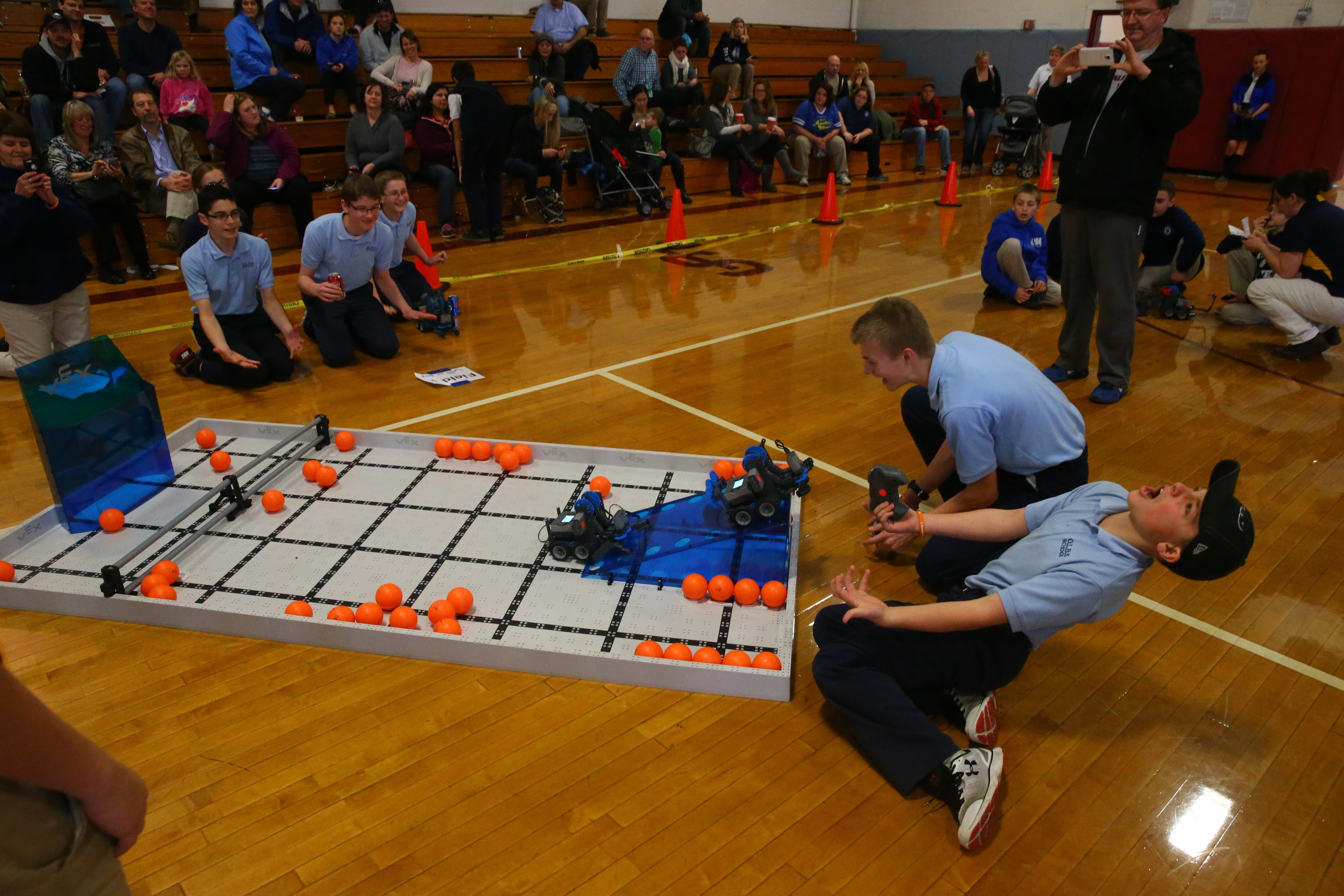 Jake Sacilowski, top right, and Matthew Walter, bottom, of Our Lady the Blessed Sacrament robotics team  react as they compete in Diocese of Buffalo's Xstream games and expo at St. Joseph Collegiate Institute Sunday.