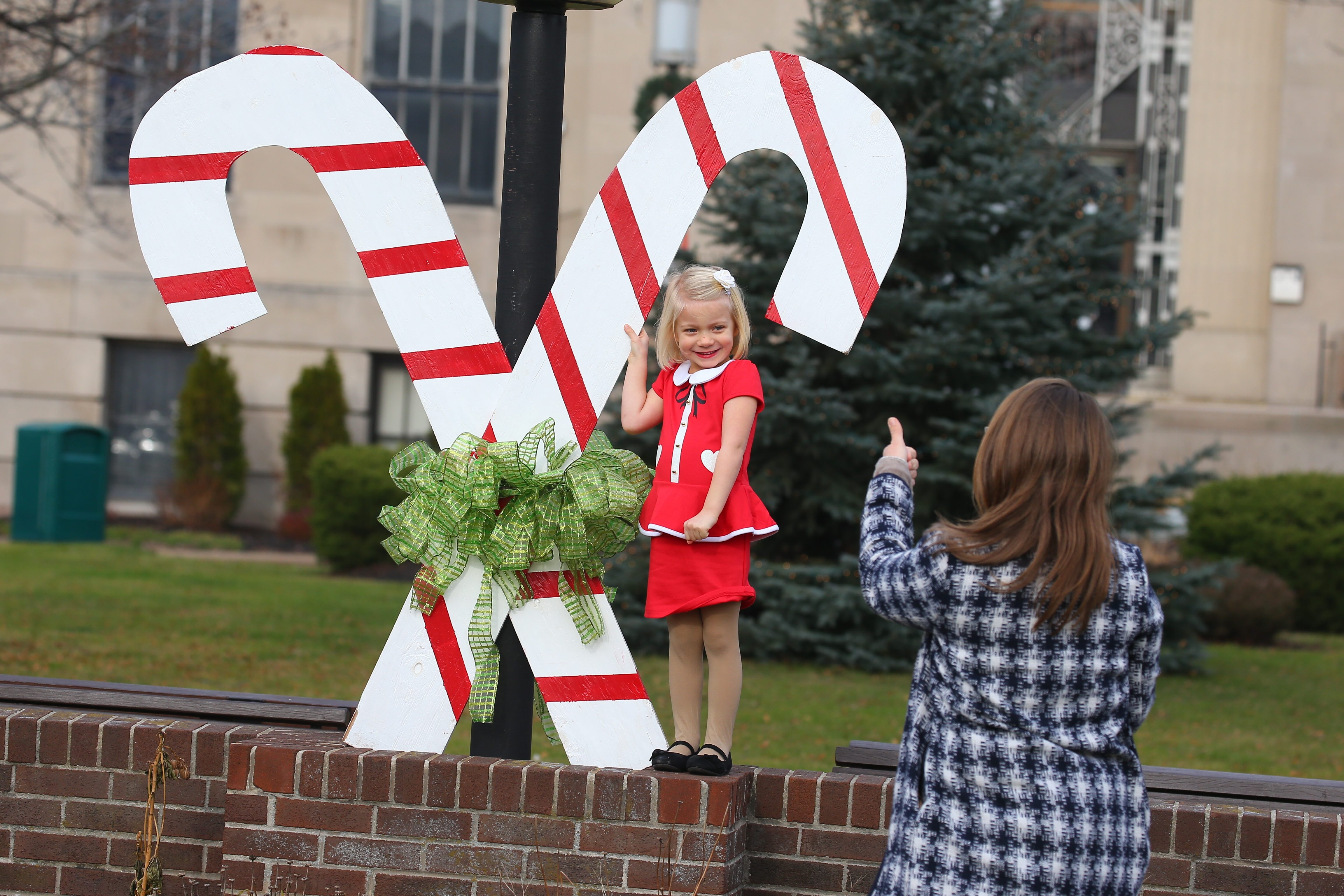 Tina Anderson and daughter Cecilia Kress, 3, don't need cold-weather jackets as they capitalize on Sunday's unusual December warmth for a holiday photo shoot at  the Kenmore-Town of Tonawanda Municipal Building. See a photo gallery at buffalonews.com.