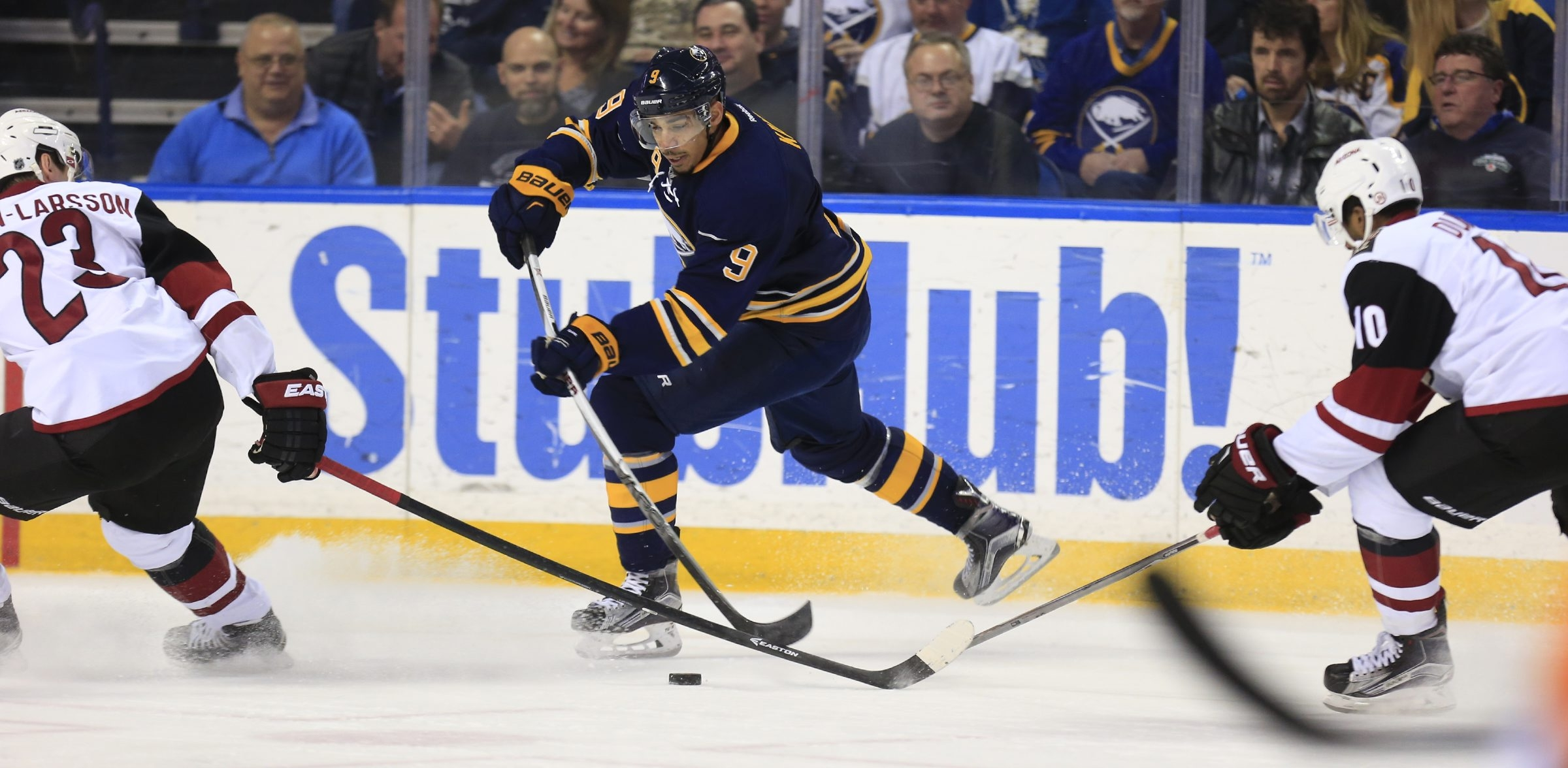 Sabres winger Evander Kane, who scored two goals for the second straight game, moves the puck between Coyotes players.
