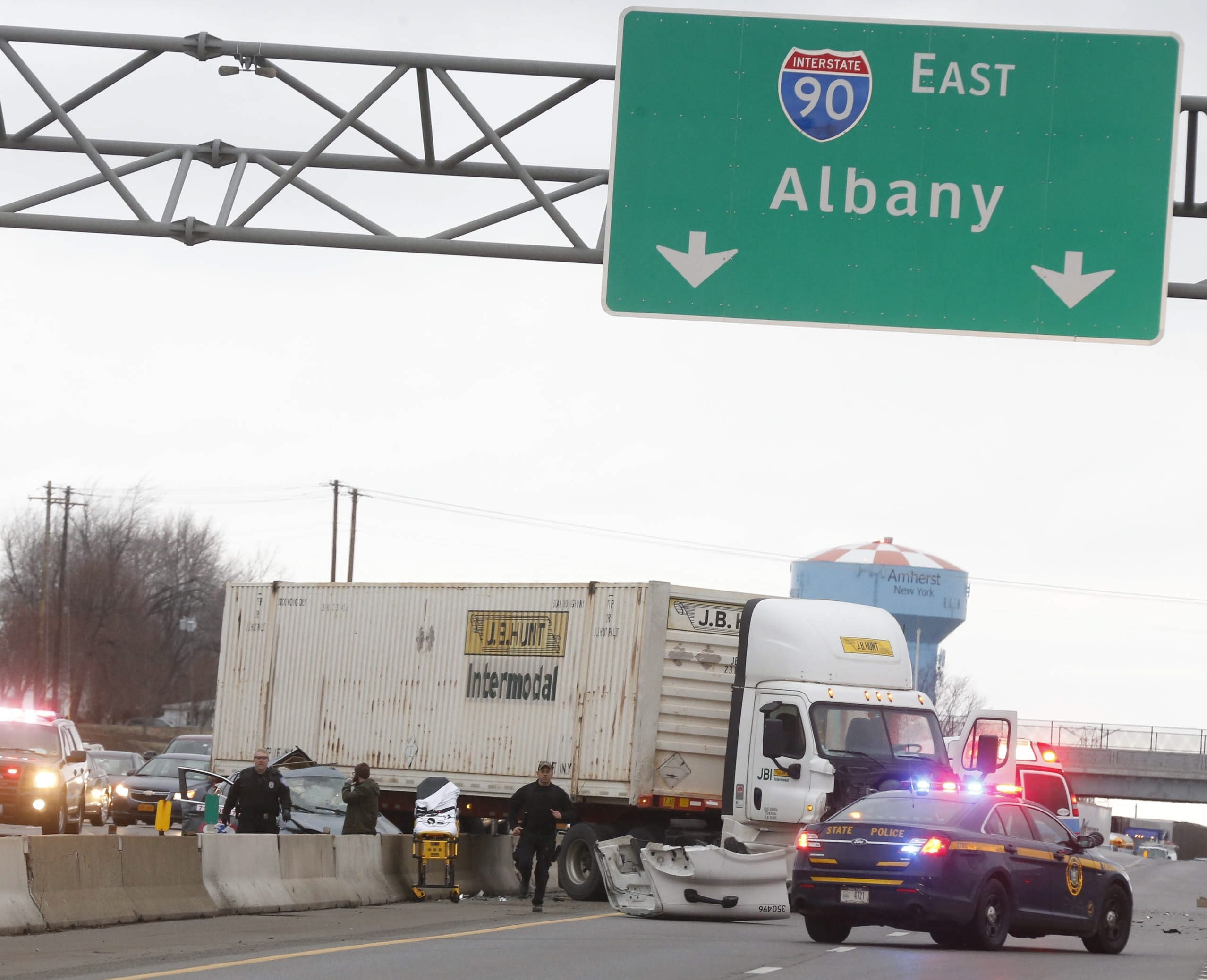 A police officer runs back to his patrol car after examining a car involved in crash that sent a tractor trailer through a concrete divider on the eastbound Thruway near the Cleveland Drive exit on Thursday.