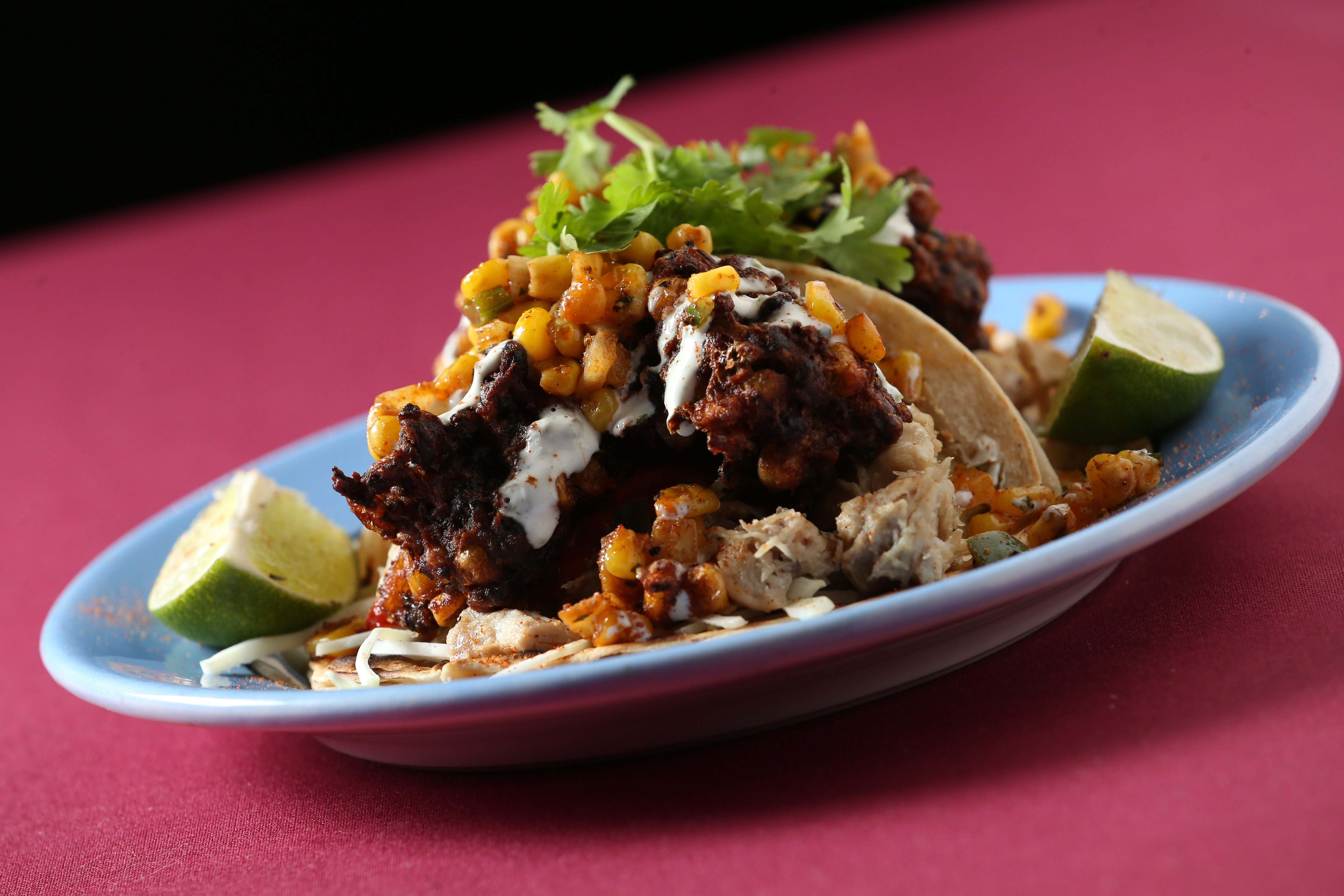 Black bean fritter, shredded chicken, roasted corn salsa, cabbage, sriracha and lime cilantro creme.
