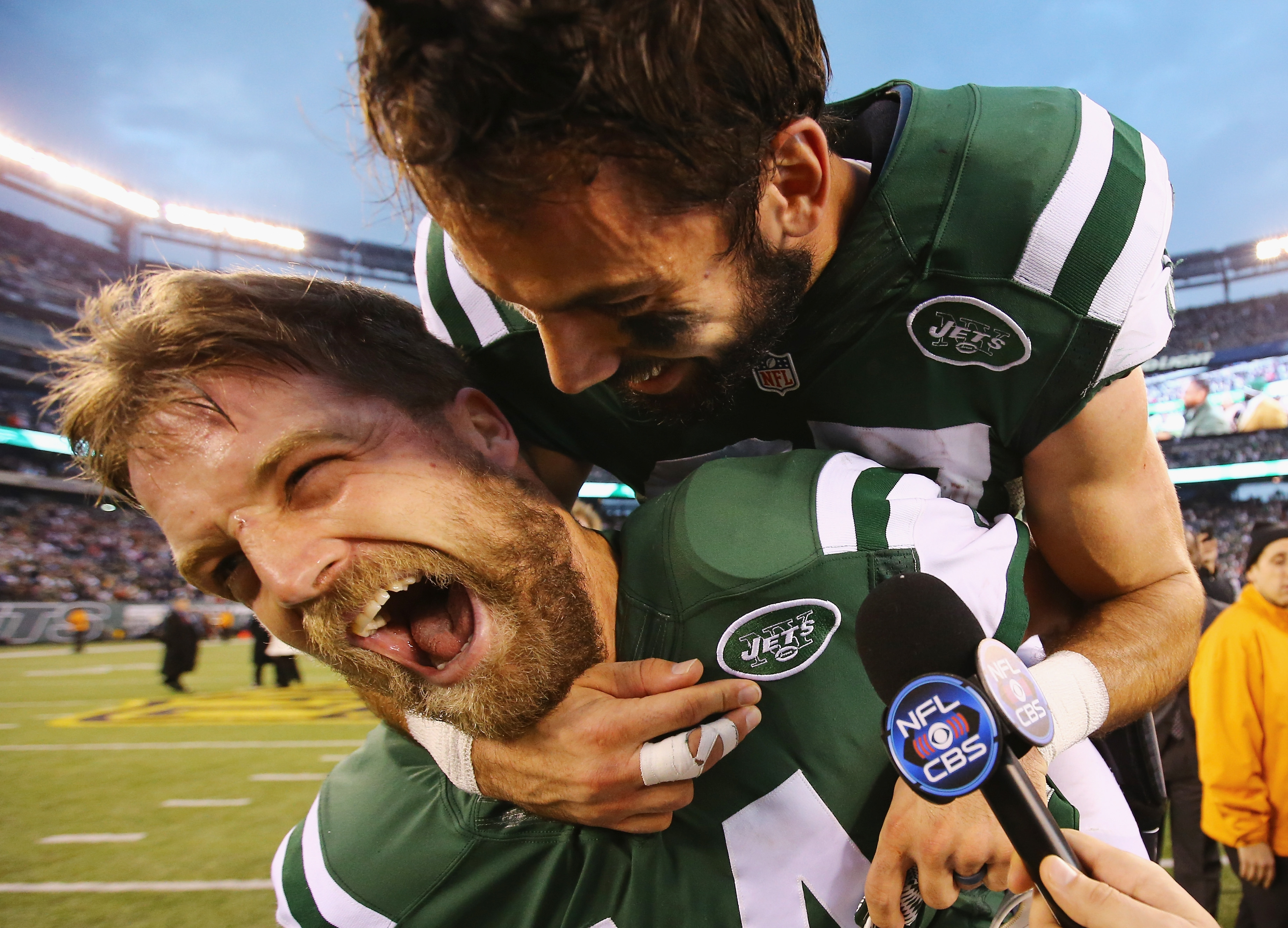 Jets quarterback Ryan Fitzpatrick, bottom, celebrates with receiver Eric Decker after defeating the New England Patriots in overtime on Sunday, setting up a high-stakes game in Orchard Park next week. (Al Bello/Getty Images)