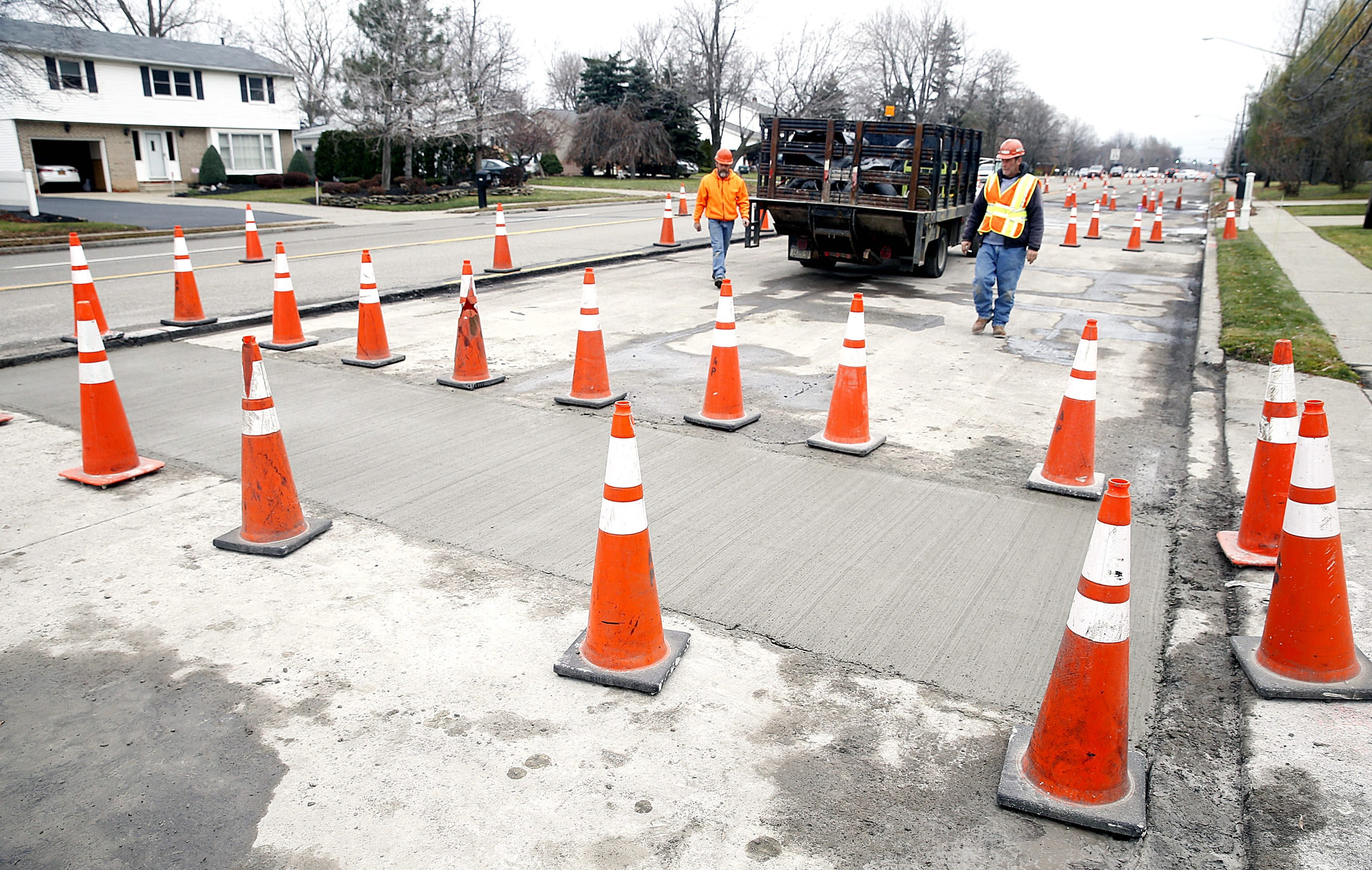 Construction workers Eric Schmidt, kneeling, and Bruce Pregitzer work on putting into place a science experiment of sorts on a stretch of Maple Road in Amherst on Dec. 2 to determine which of several repaving methods is most effective.