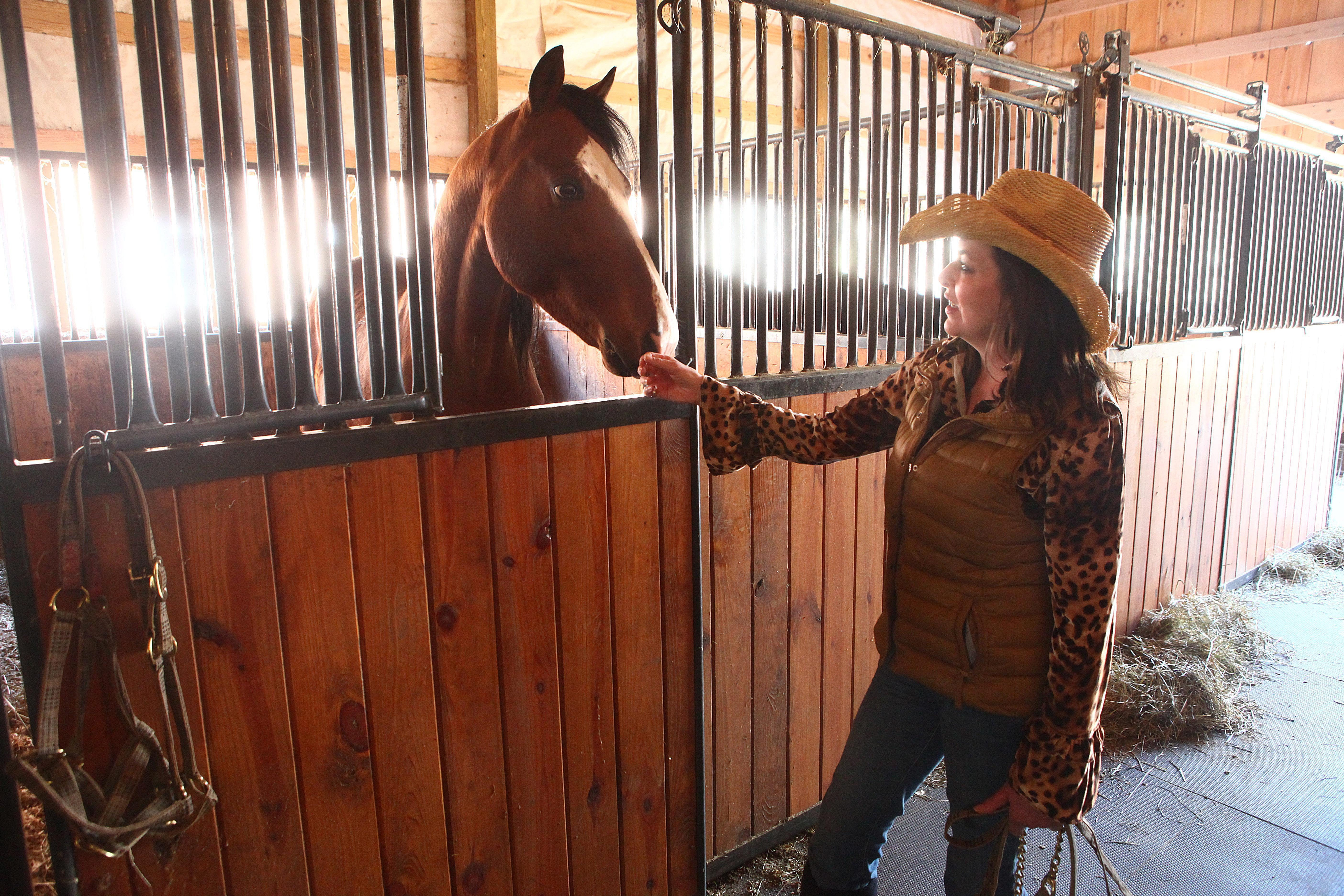 A file photo shows Beth Lynn Hoskins at her stable in Aurora with one of her horses.