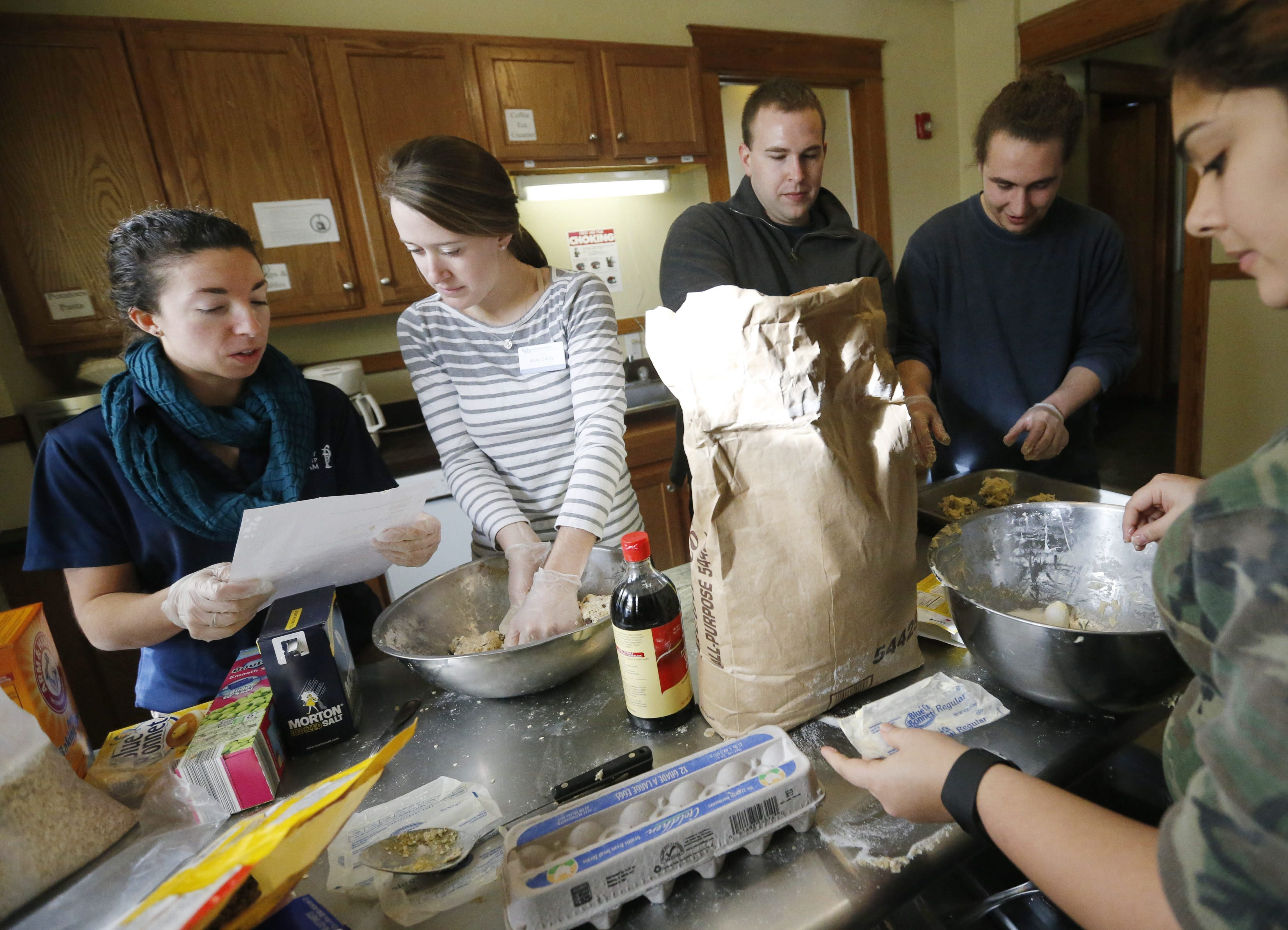 """""""Prosperity Fellows"""" from UB, who receive financial aid in return for promising to stay in Buffalo after graduation, make cookies for residents Monday at the Bissonette House on Grider Street."""