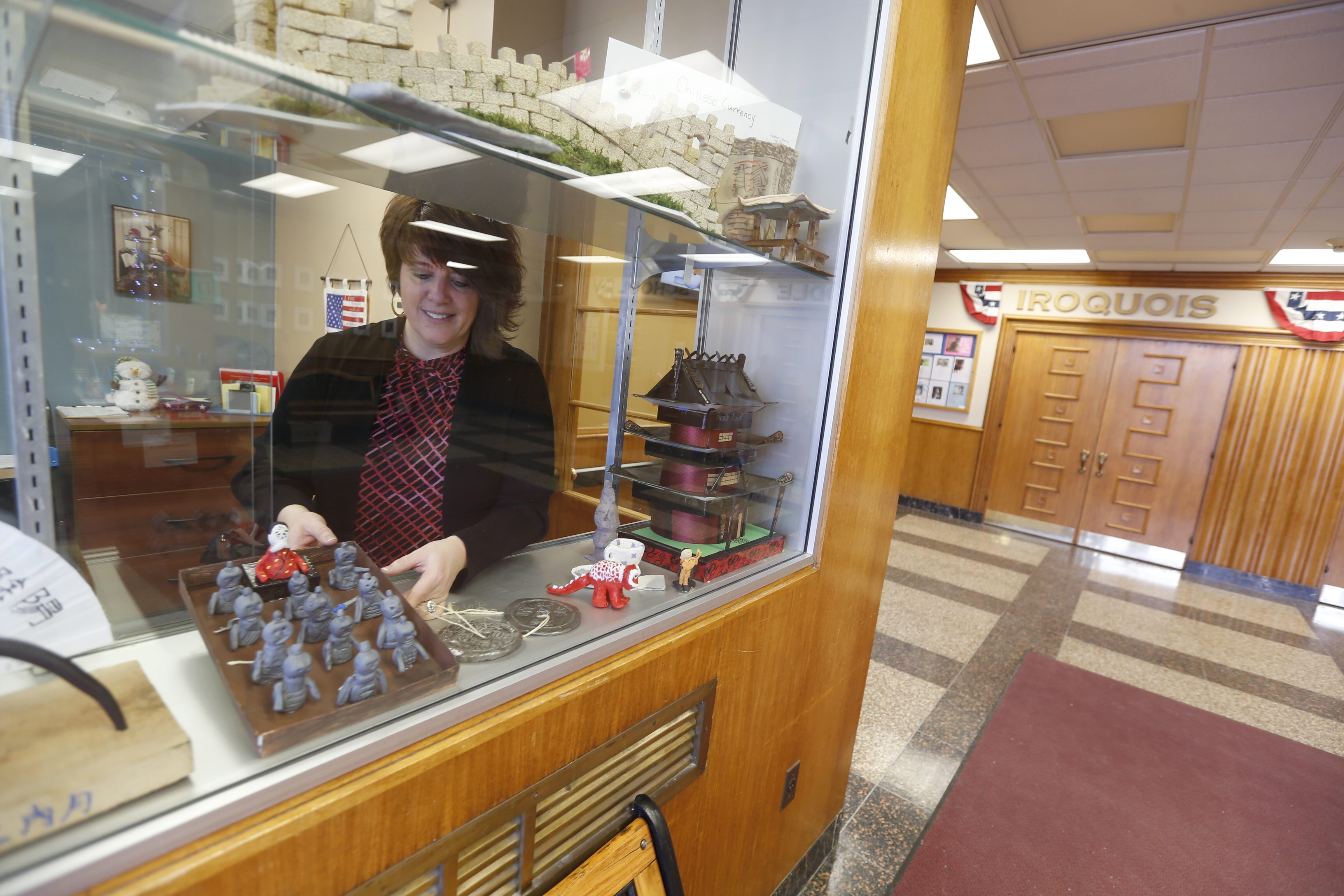 """Iroquois Middle School social studies teacher Karen Reid  decorates the front lobby of the middle school with student projects Jan. 19. One of the propositions voters will decide today would add """"security zones"""" to this lobby. (Robert Kirkham/Buffalo News)"""