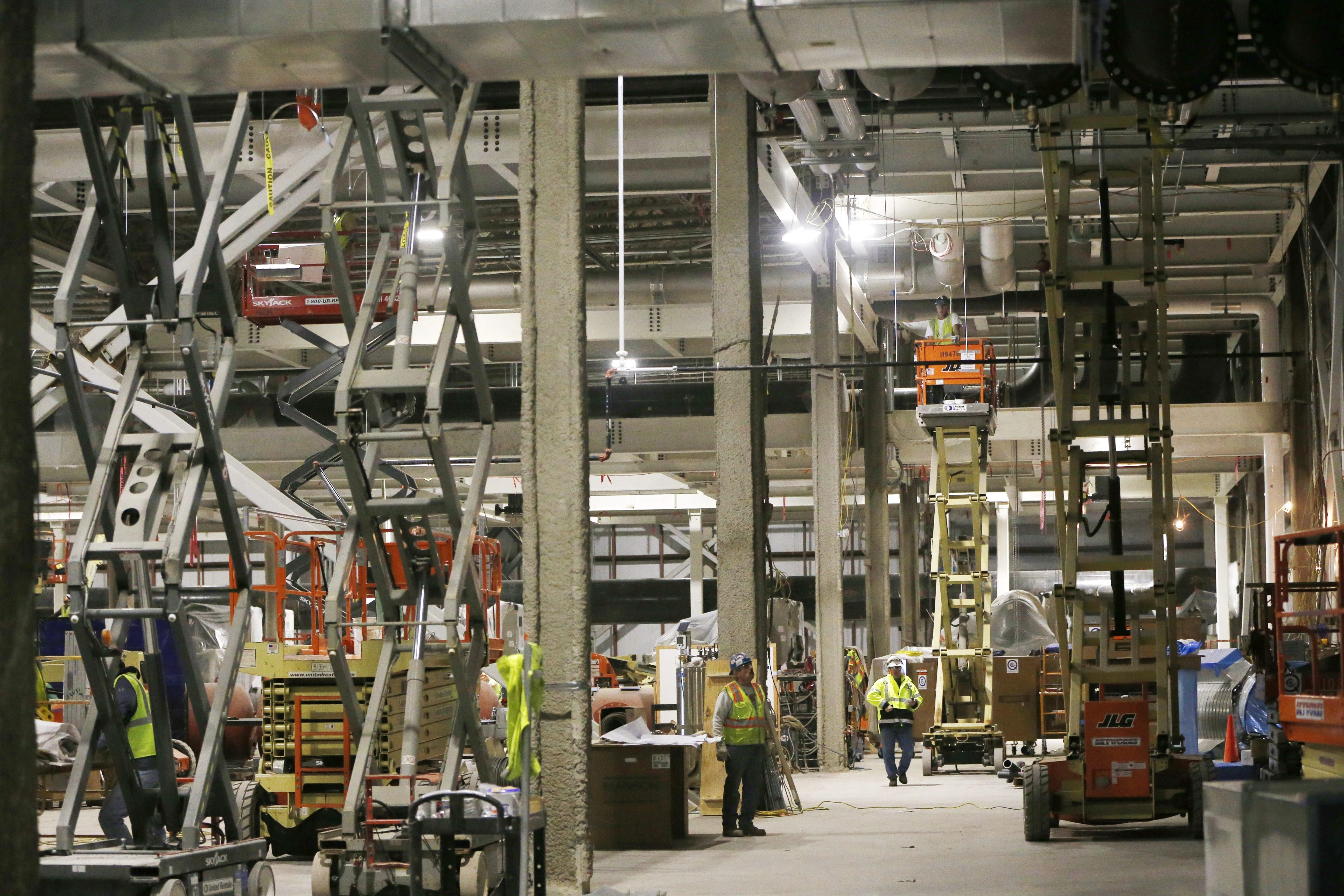 Workers install utilities in the enormous mechanical building at the SolarCity production facility at RiverBend earlier this month. Construction jobs at SolarCity and the Buffalo Niagara Medical Campus have helped to keep the region's unemployment rate down.
