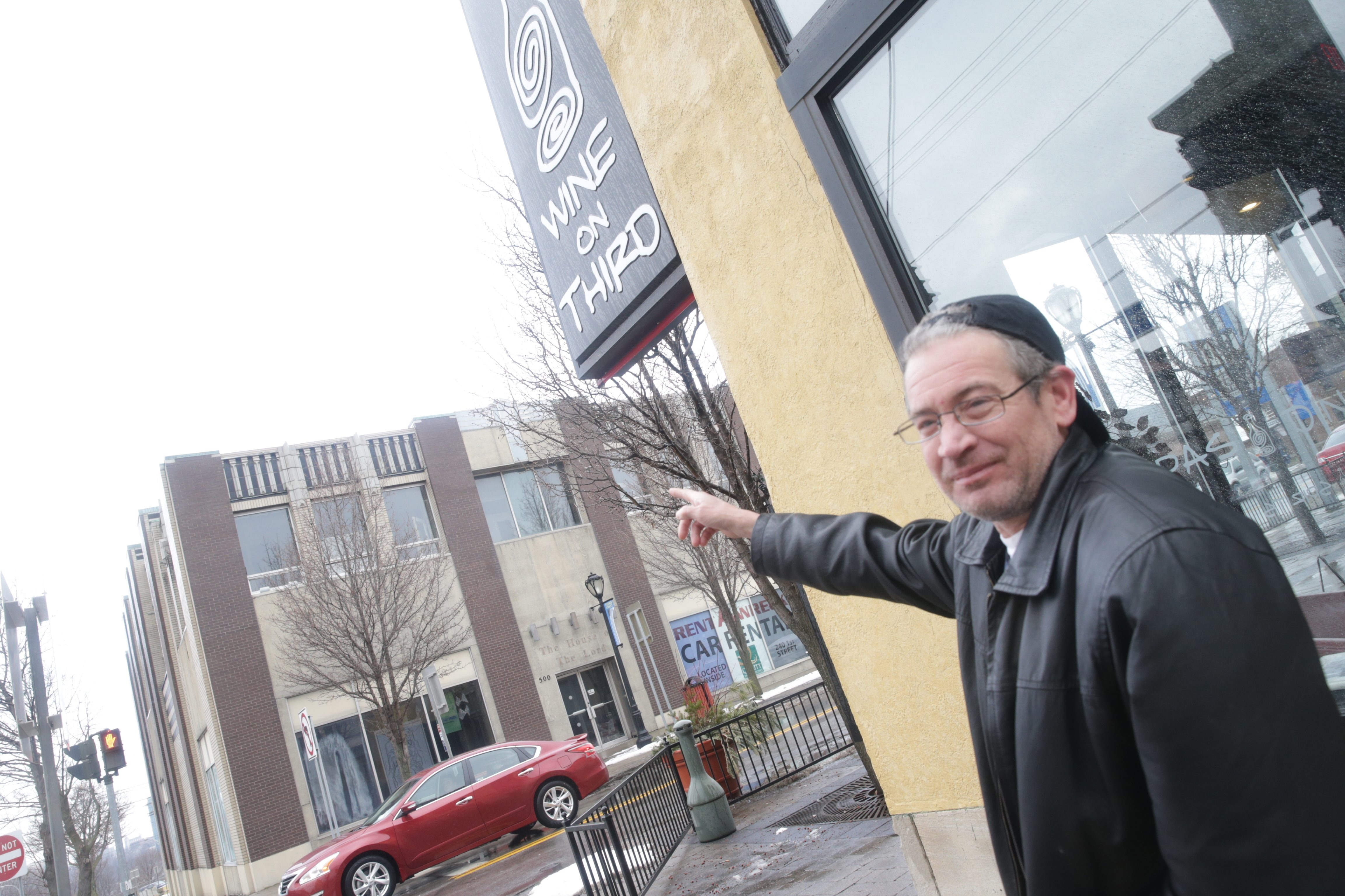 Kevin Robertson, a chef at Wine on Third, points to the vacant building at Ferry and Third streets where every day from 3 to 11 p.m. a loop of the University of Iowa fight song can be heard.