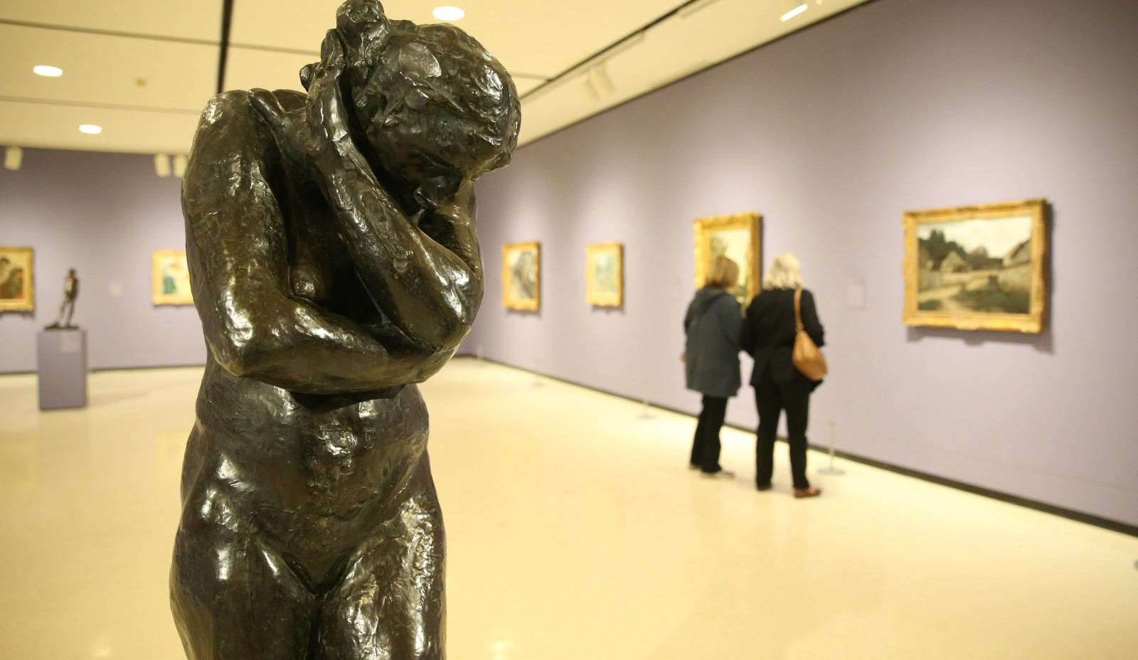 """Meditative moments: """"Eve"""" by Auguste Rodin dominates the floor while visitors to the Albright-Knox look at the Monet exhibit. Below left, sisters Patti and Clare Beaulieu head through the columns into the gallery. (Sharon Cantillon/Buffalo News)"""