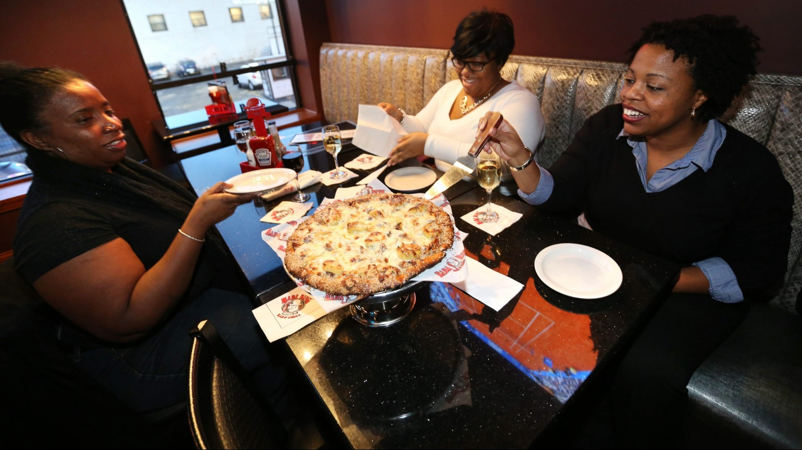 LaTonya Porter, left, of Buffalo, Shantey Brown, of Blasdell, and Stephaine Huston, of Niagara Falls, enjoy the steak and stuffed pepper pizza at Bada Bing. (Sharon Cantillon/Buffalo News)