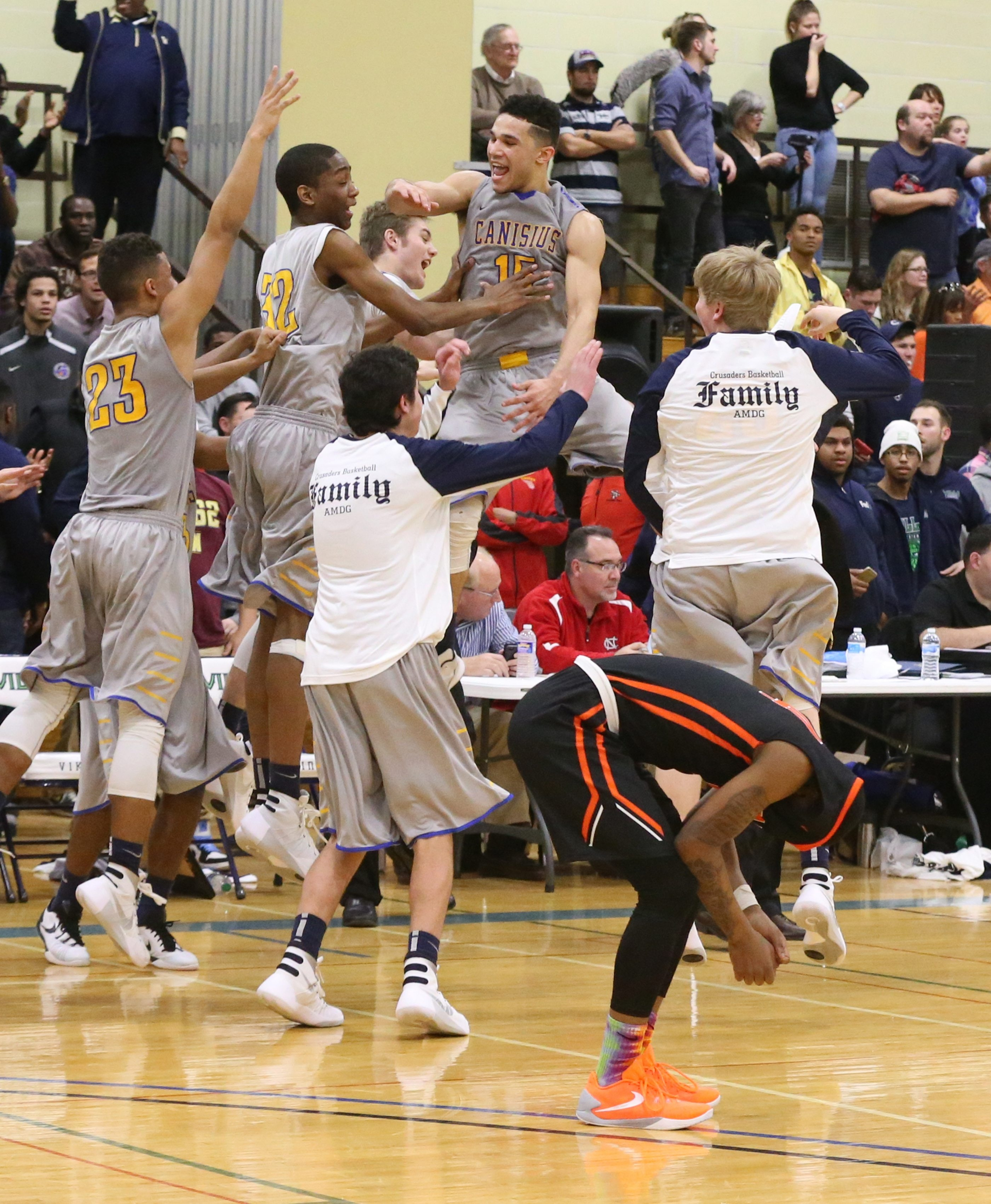 Canisius Crusaders Justin Jones takes the high road to celebrate with his team after defeating Park  in overtime before a standing-room only crowd at Villa Maria College on Sunday.