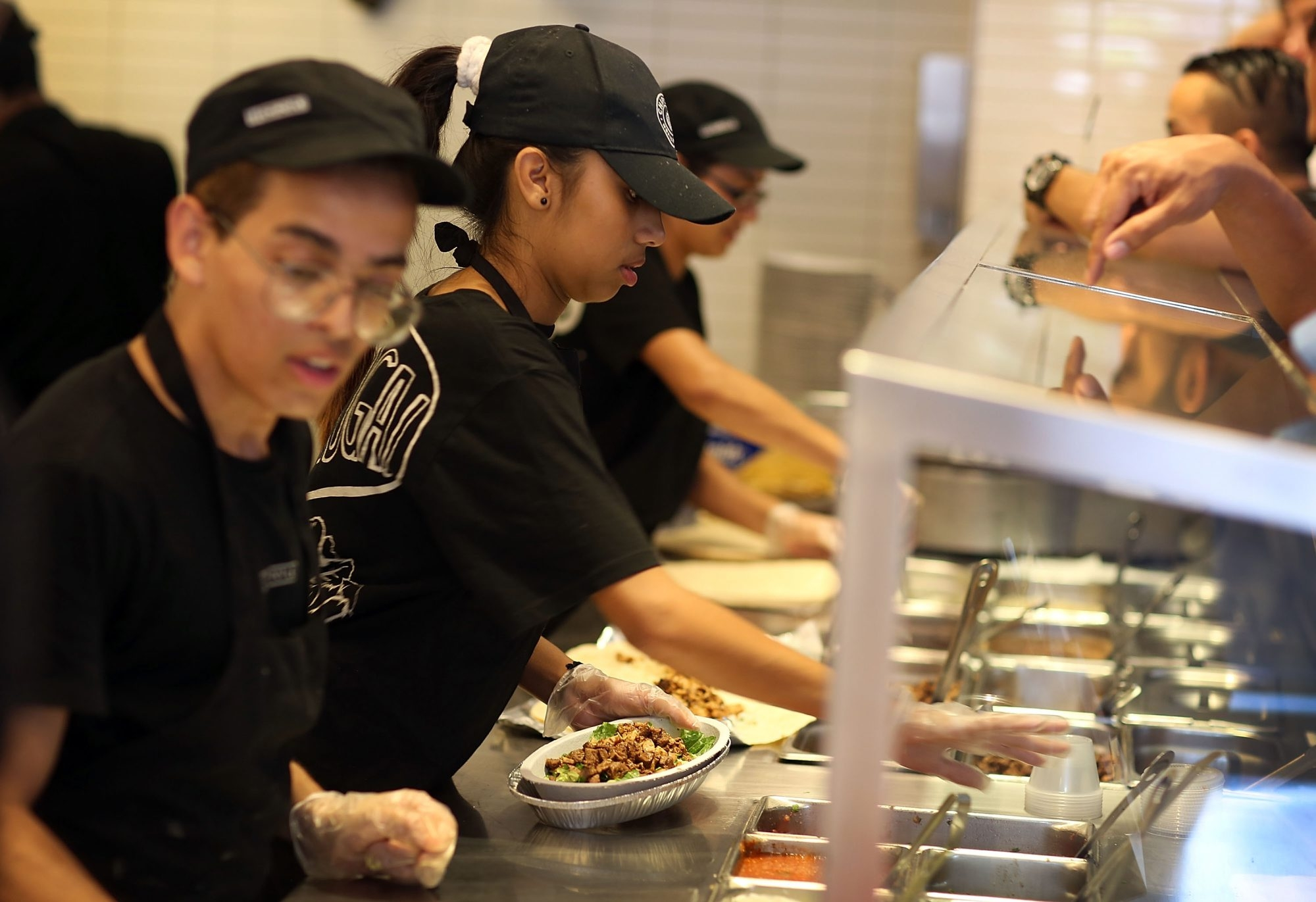 Chipotle Mexican Grill restaurant workers fill orders for customers in Miami, Fla.