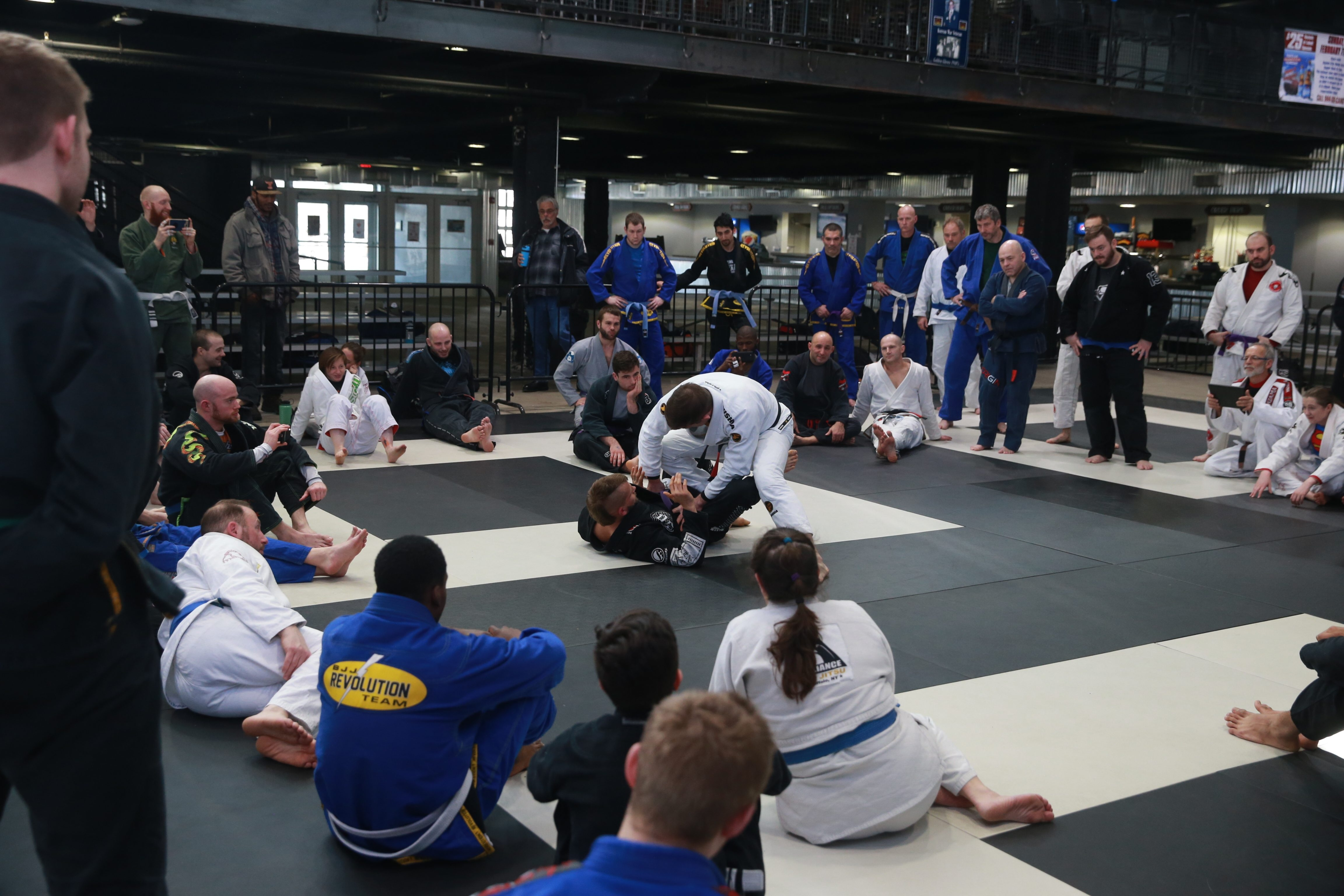 Michael Katilus, in white, demonstrates a move with Jordan Marwin, in black, at a jiu jitsu seminar at Buffalo Riverworks on Saturday. More than 60 people donated at least $30 apiece to take part in the event, a benefit to help Paul Moran pay his cancer treatment bills.