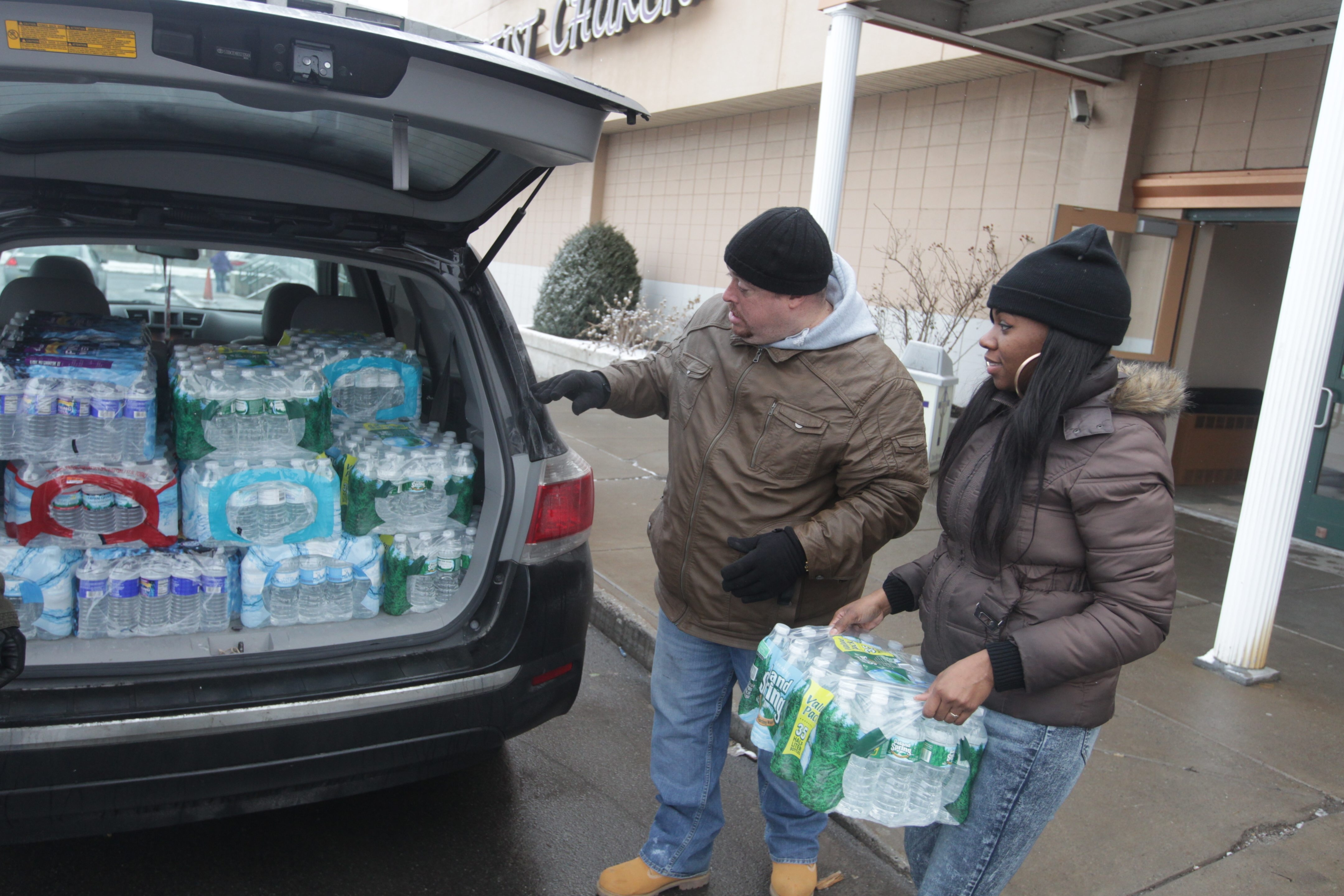 Don Allen Jr., left, and Lois Buchanan load cases of water into Bob Rich III's vehicle on Friday. Several dozen volunteers from Buffalo and Syracuse teamed up for Operation H2O to deliver bottled water to residents in Flint, Mich.  (John Hickey/Buffalo News)