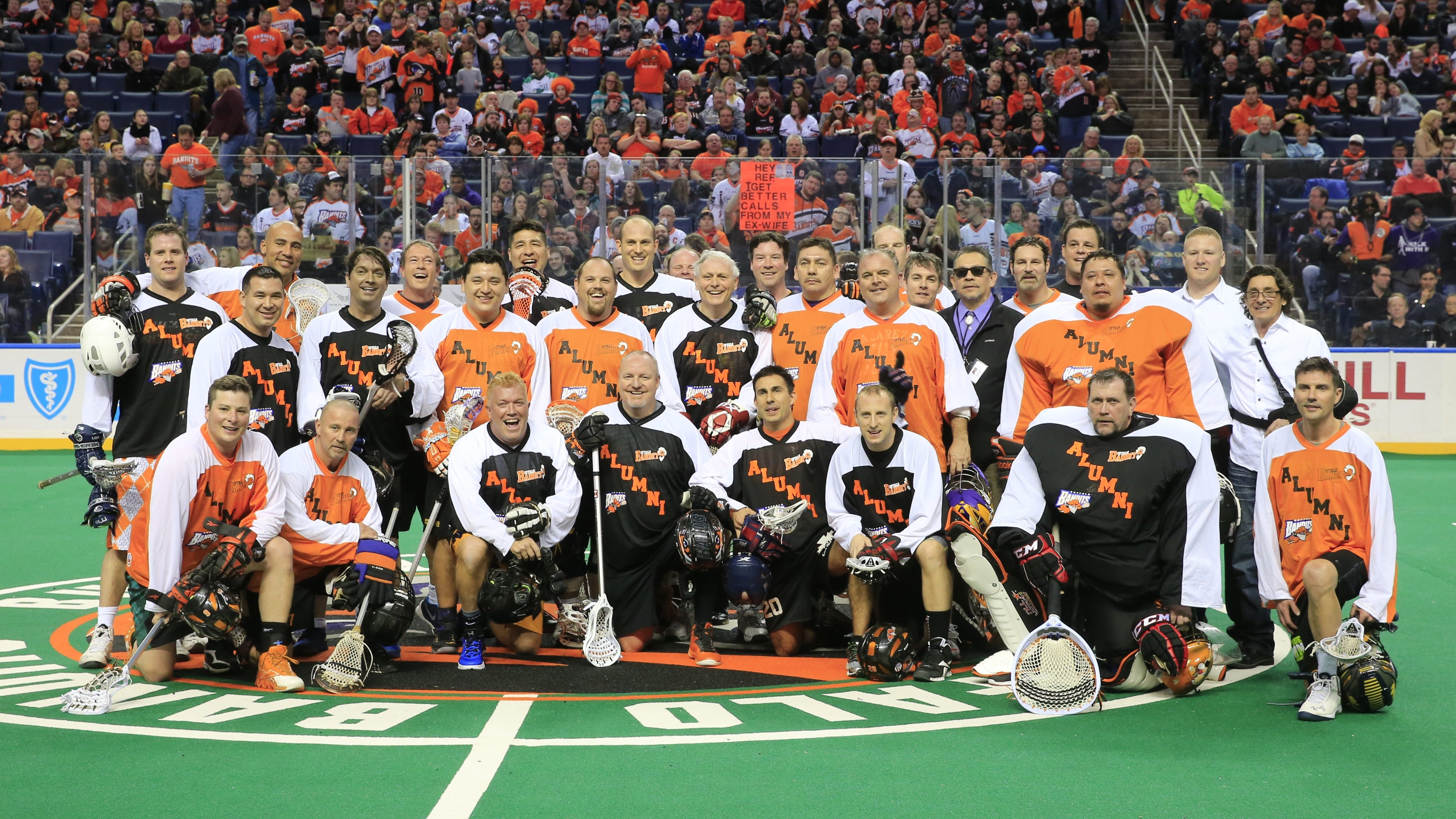 Members of past Buffalo Bandits championship teams pose for a team photo after a exhibition game at halftime of the game with the New England Black Wolves Saturday at First Niagara Center.