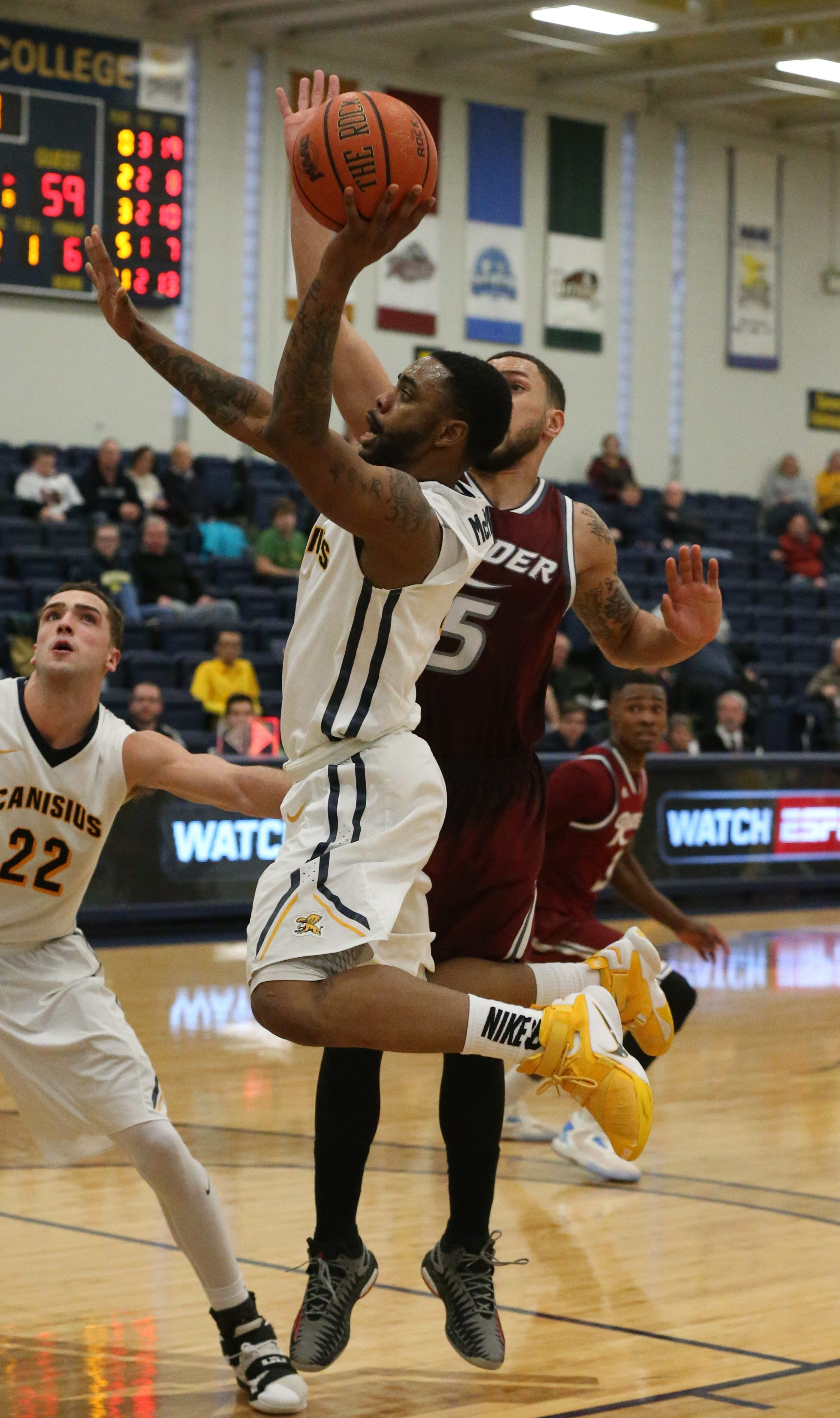 Canisius guard Malcolm McMillan, driving against Teddy Okereafor of Rider, scored 10 points for the Golden Griffins.