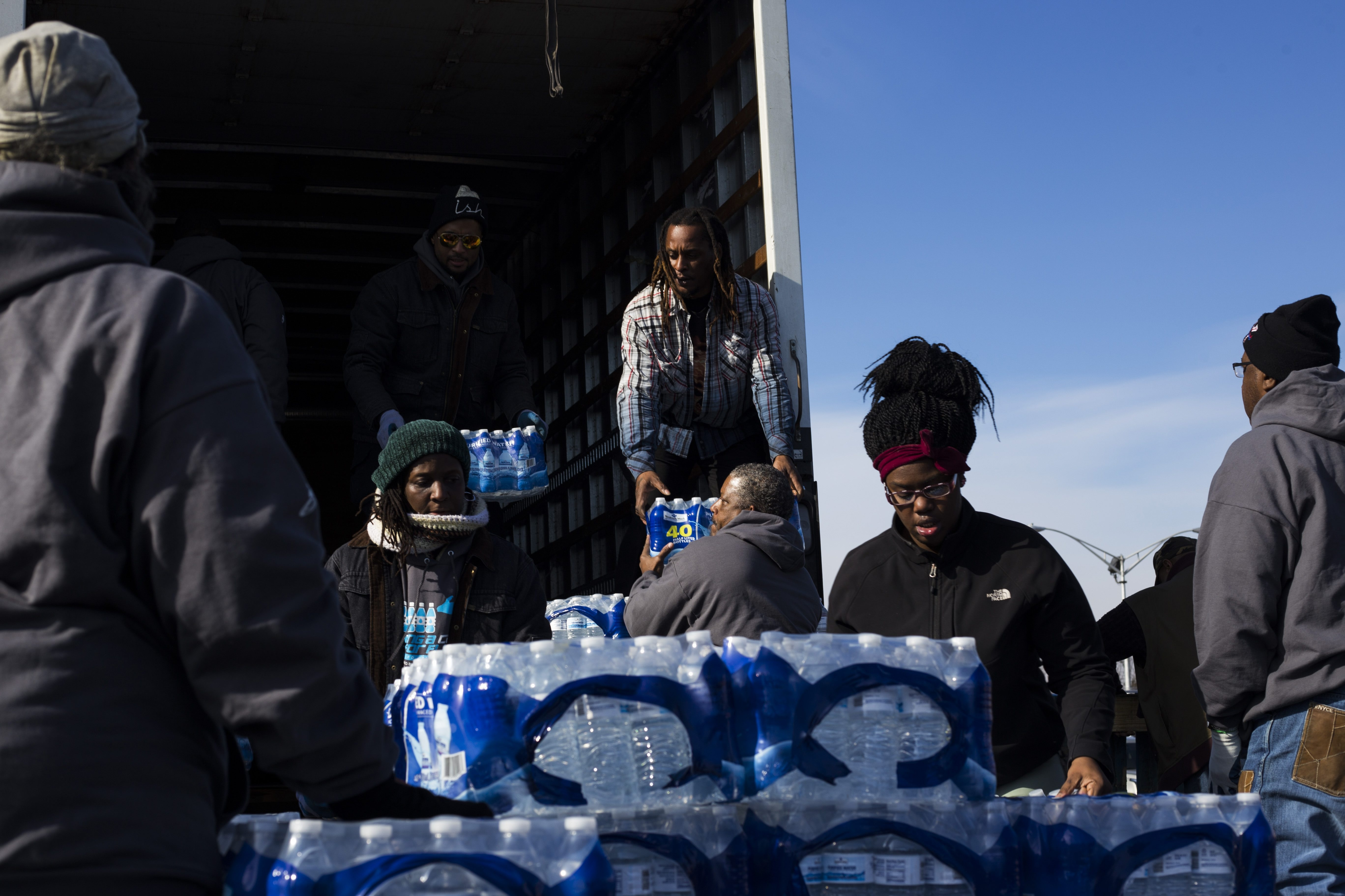 Volunteers stack cases of bottled water to hand out to a line of cars during a water drive put on in the North side of Flint, one of the areas most effected by the city's ongoing water crisis, on Saturday, February 6, 2016. Volunteers visited the city from both Syracuse and Buffalo, New York, to help address issues with access to fresh water. (Photo by Brittany Greeson for The Buffalo News)