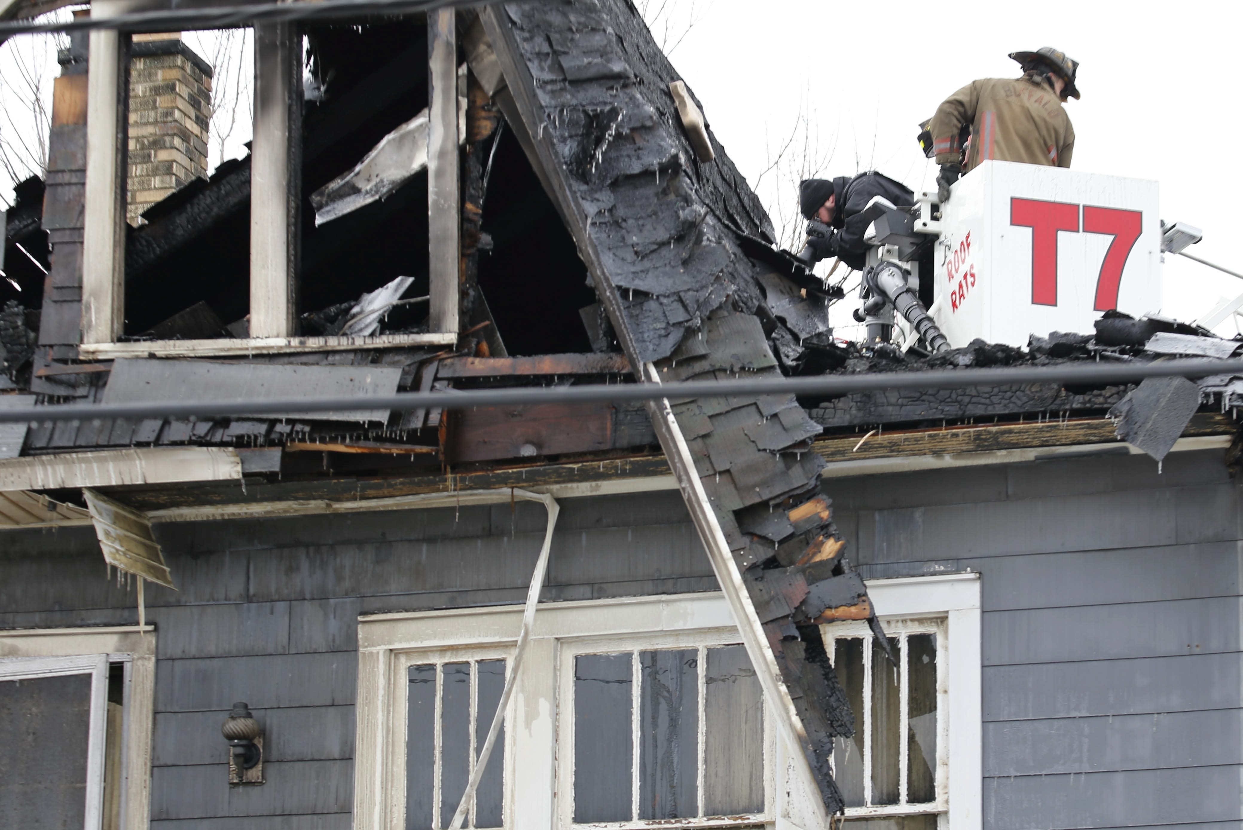 Police and fire investigators use a ladder truck to collect photographic evidence after a fire tore through 90 Humber Ave. early Friday morning, killing two and critically injuring a 9-year-old girl, Feb. 19, 2016.  (Derek Gee/Buffalo News)