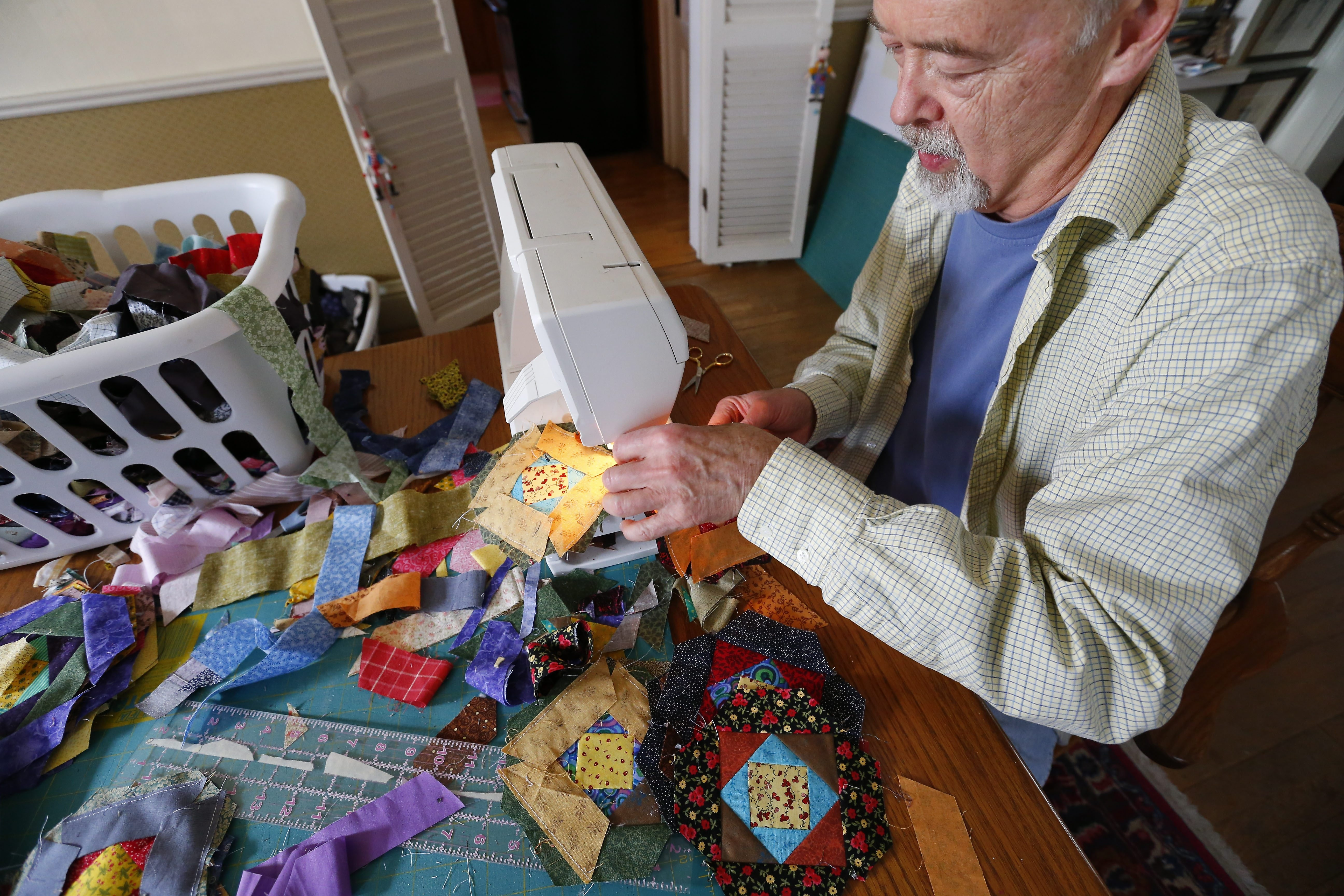 Hamburg librarian Jack Edson stitches together quilting squares he will assemble into a fabric replica of a famous portrait.