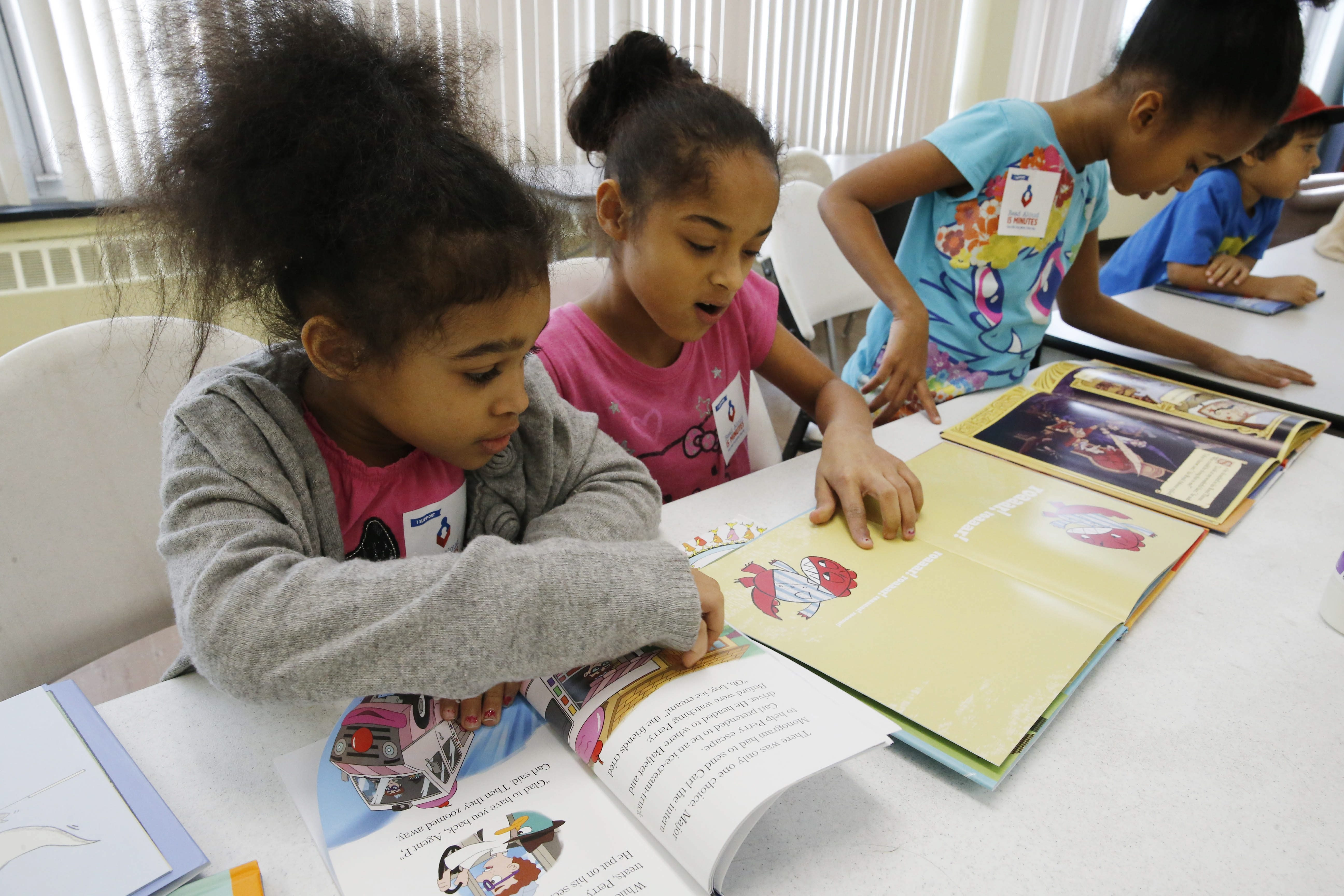 Salvation Army Kids Club members, from left, Courtlynn Paris, 6, Suzie Williams, 10, and Courtney Paris, 7, read together during Friday's launch of the Books for Kids campaign.