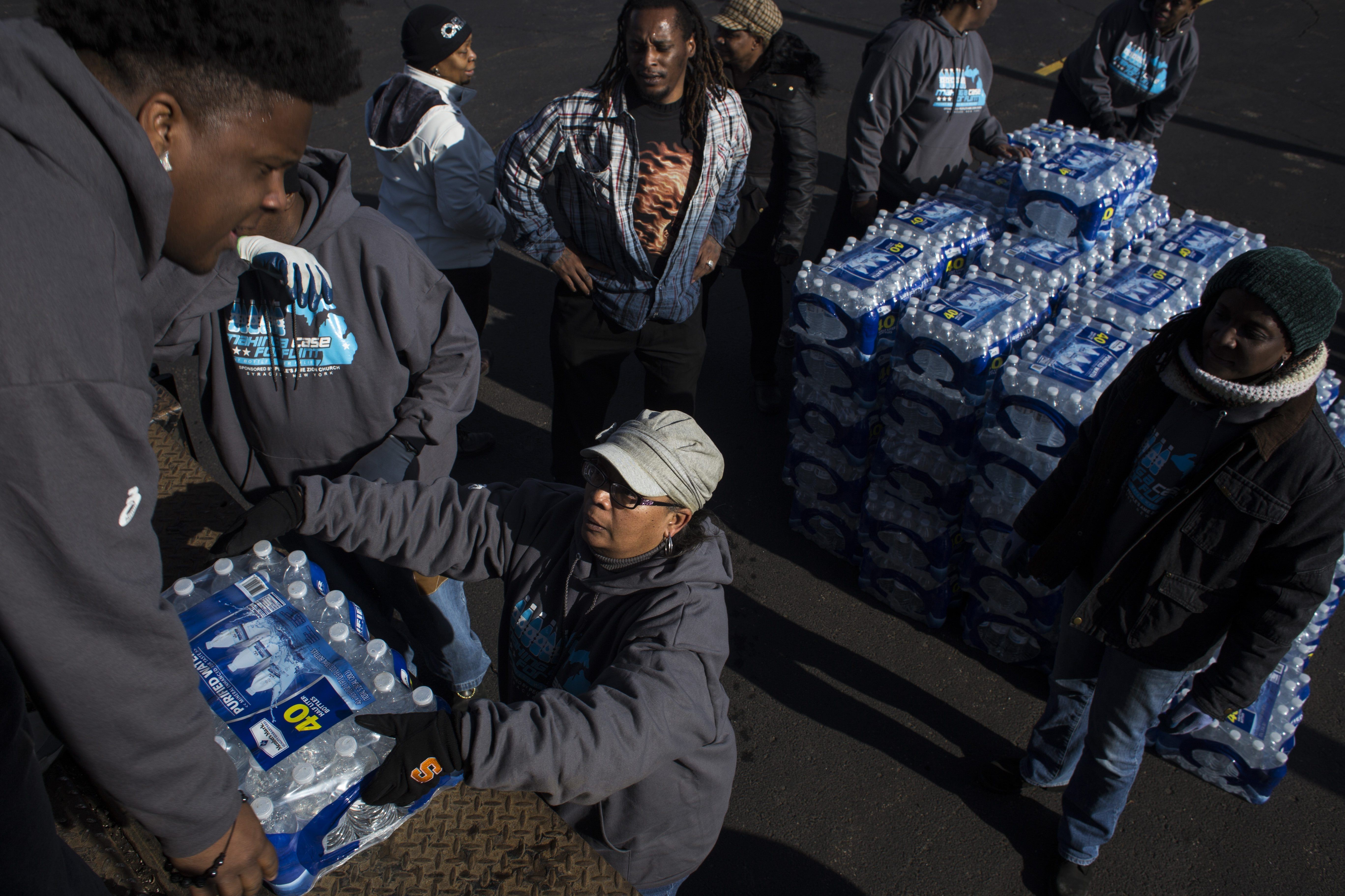 Volunteers stack cases of bottled water to hand out to a line of cars during a water drive put on in the North side of Flint, Mich., one of the areas most affected by the city's ongoing water crisis, on Feb. 6, 2016. Volunteers visited the city from both Syracuse and Buffalo to help address issues with access to fresh water. (Photo by Brittany Greeson for The Buffalo News)