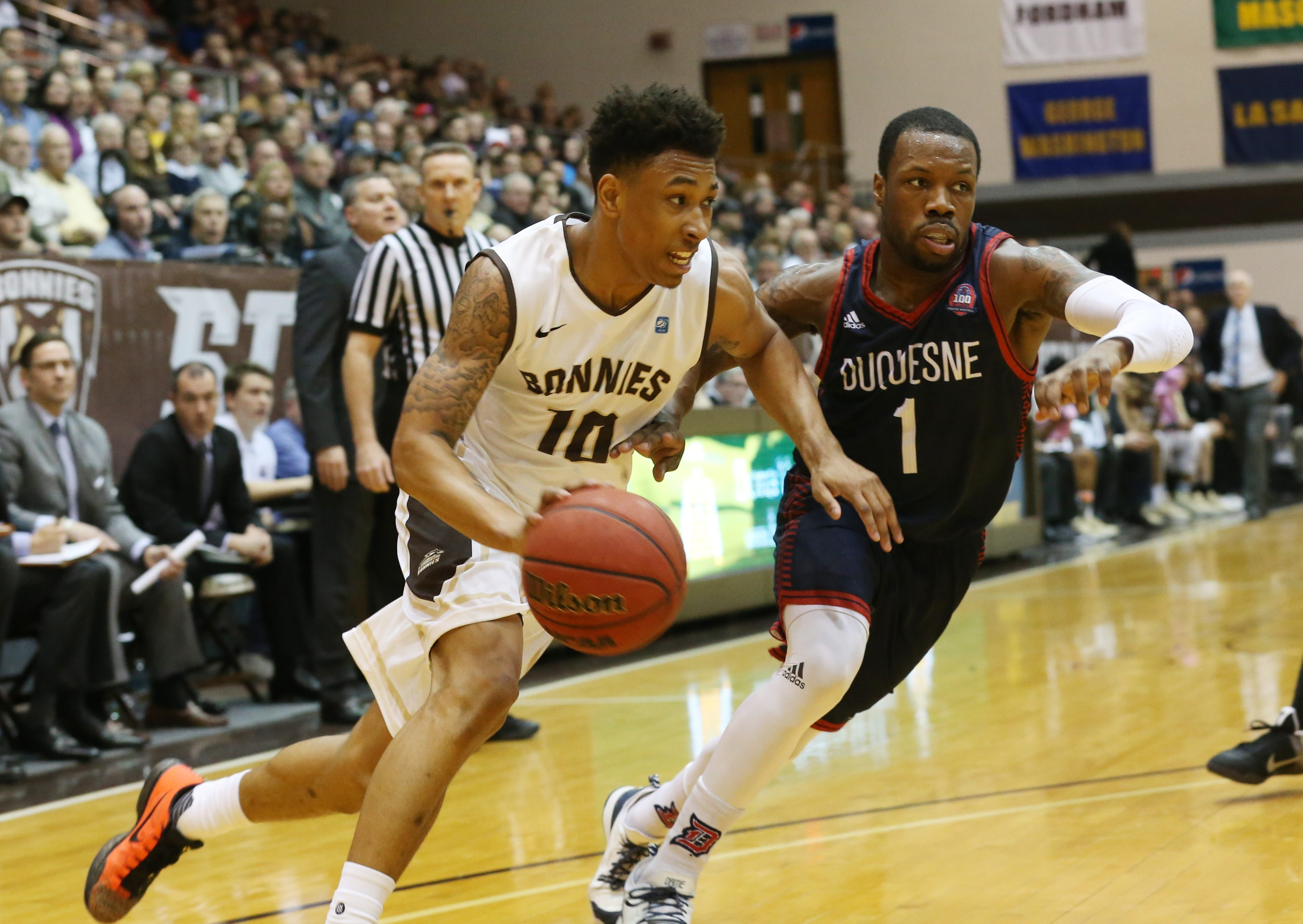 St. Bonaventure's Jaylen Adams drives to the basket while Duquesne's Derrick Lewis gives chase at the Reilly Center on Wednesday evening. The Bonnies posted an 80-76 victory. (Sharon Cantillon/Buffalo News)