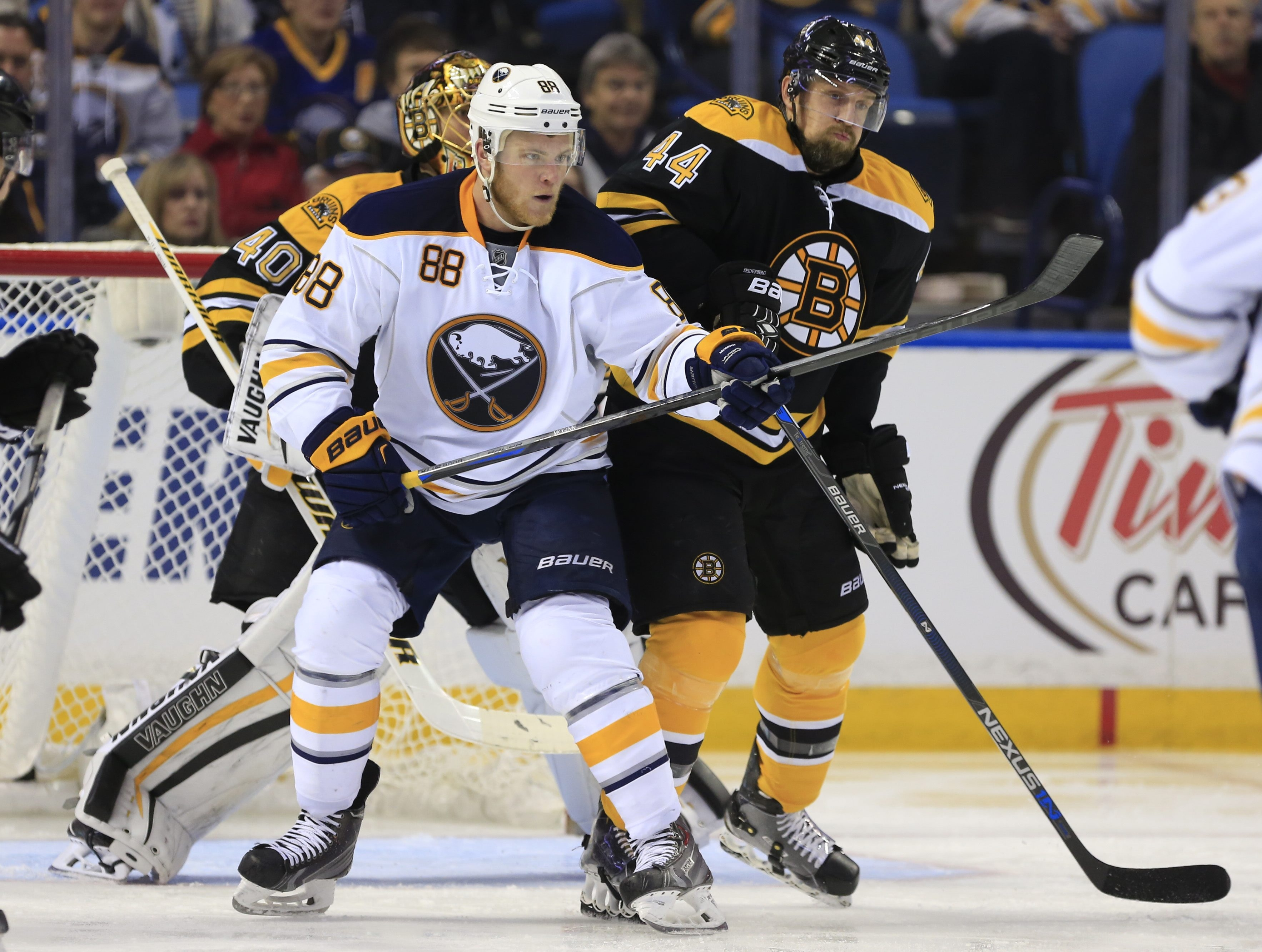 Jamie McGinn, who has had a solid season for the Sabres, tips the puck past Boston's Dennis Seidenberg in the third period. (Harry Scull Jr./Buffalo News)