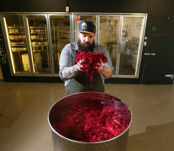 RJ Marvin, owner of Barrel + Brine, massages beet and caraway sauerkraut at his West Side fermented foods shop. (Photos by Sharon Cantillon/Buffalo News)