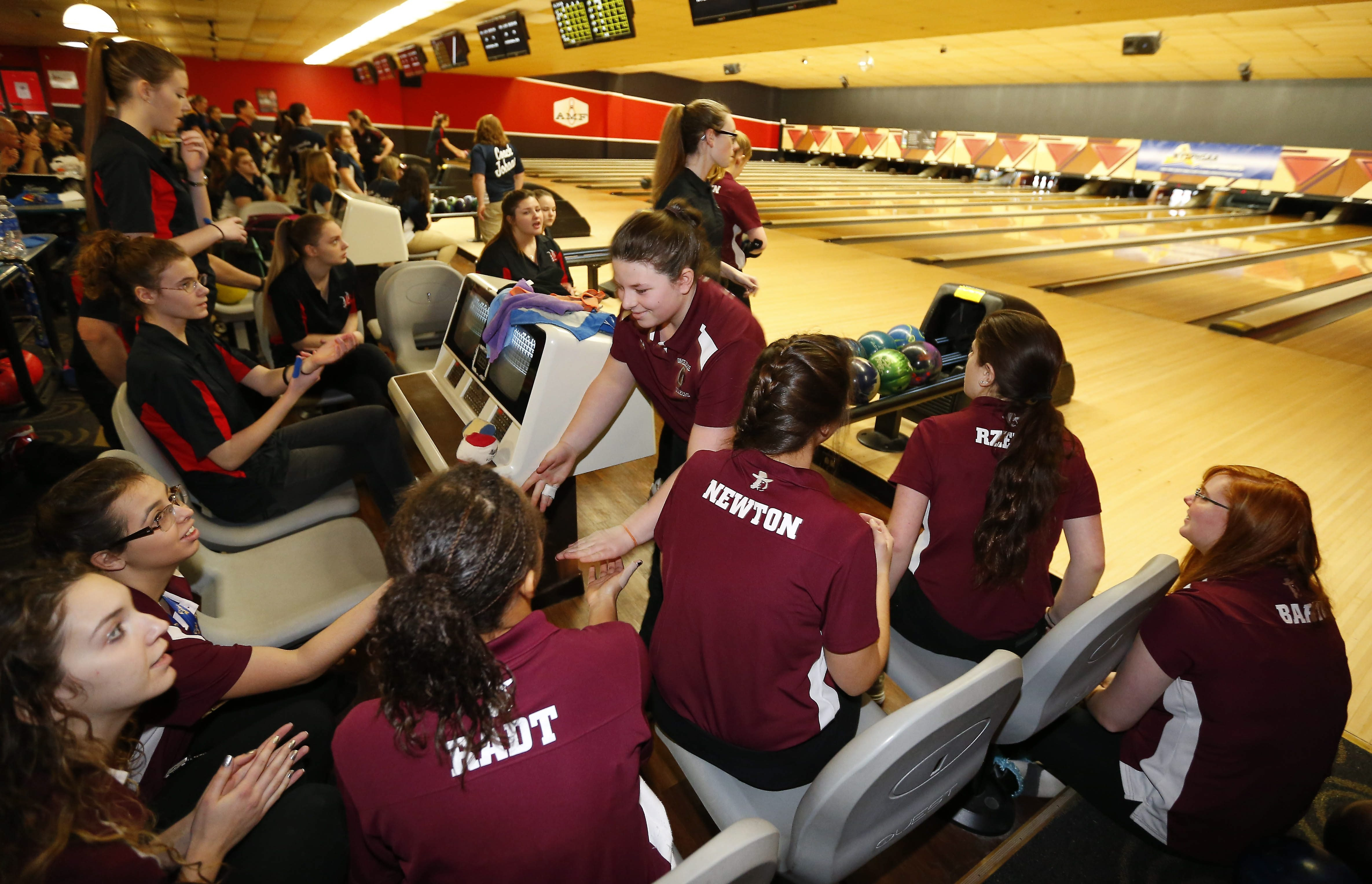 Orchard Park's Danielle Milo is congratulated by her teammates after throwing a strike during the New York State Public High School Athletic Association bowling championships at Airport Lanes.