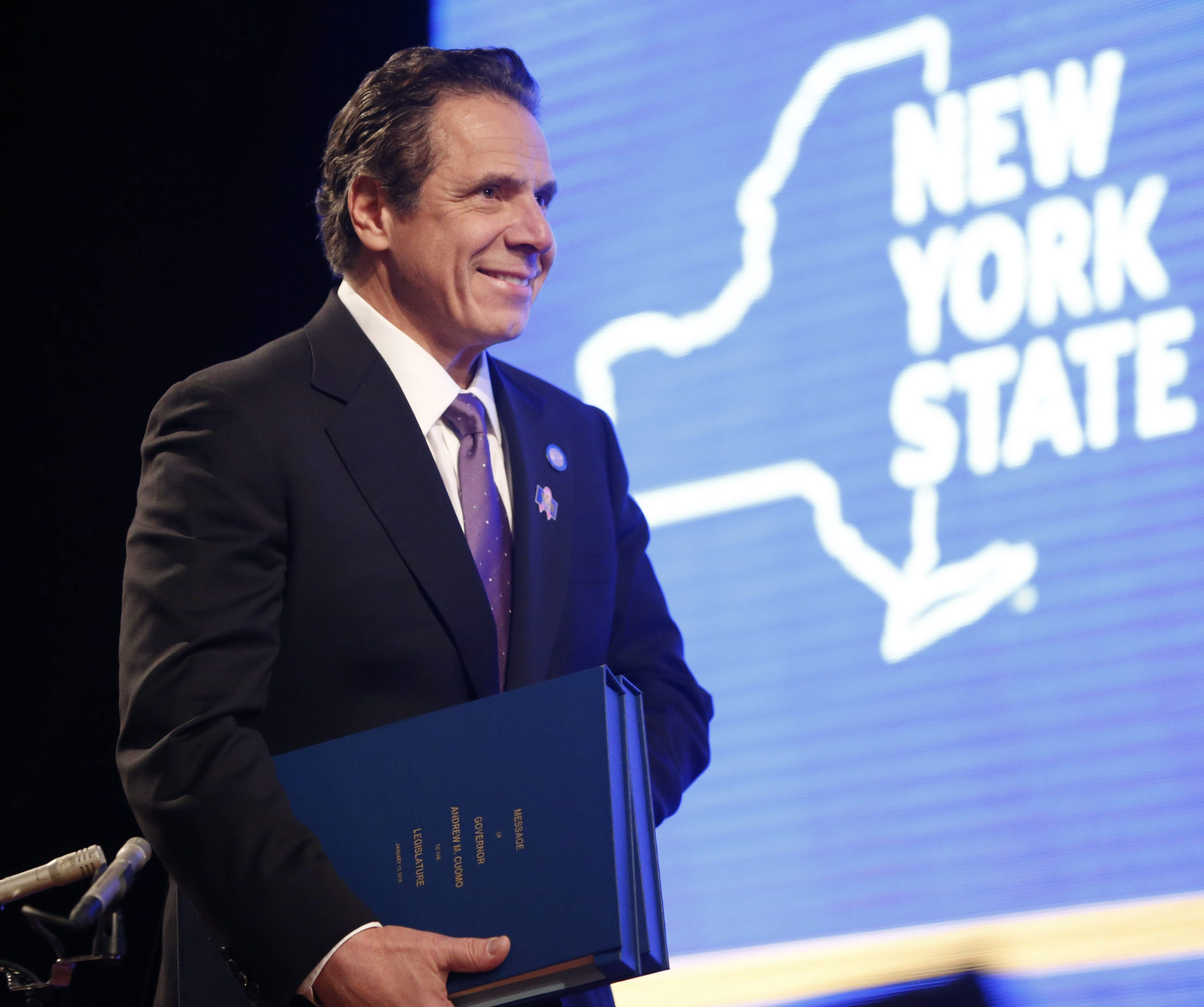 With copies of his budget in hand, New York Gov. Andrew Cuomo takes the stage for the annual State of the State address at the Empire State Plaza Convention Center in Albany, Wednesday, Jan. 13, 2016.  (Derek Gee/Buffalo News)