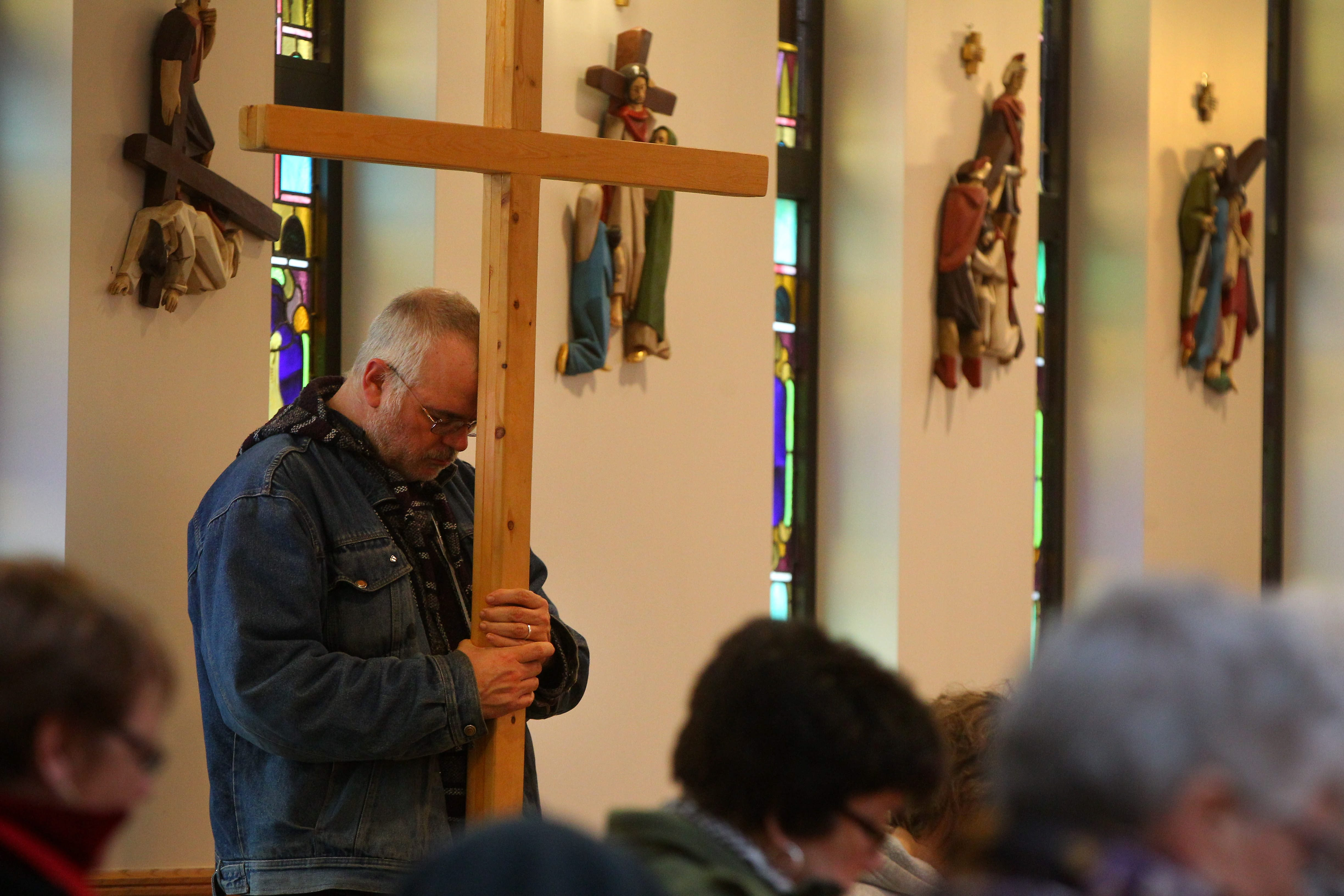 Matt Boyle carries the cross during the Stations of the Cross service commemorating 10th anniversary of Sister Karen Klimczak's death.