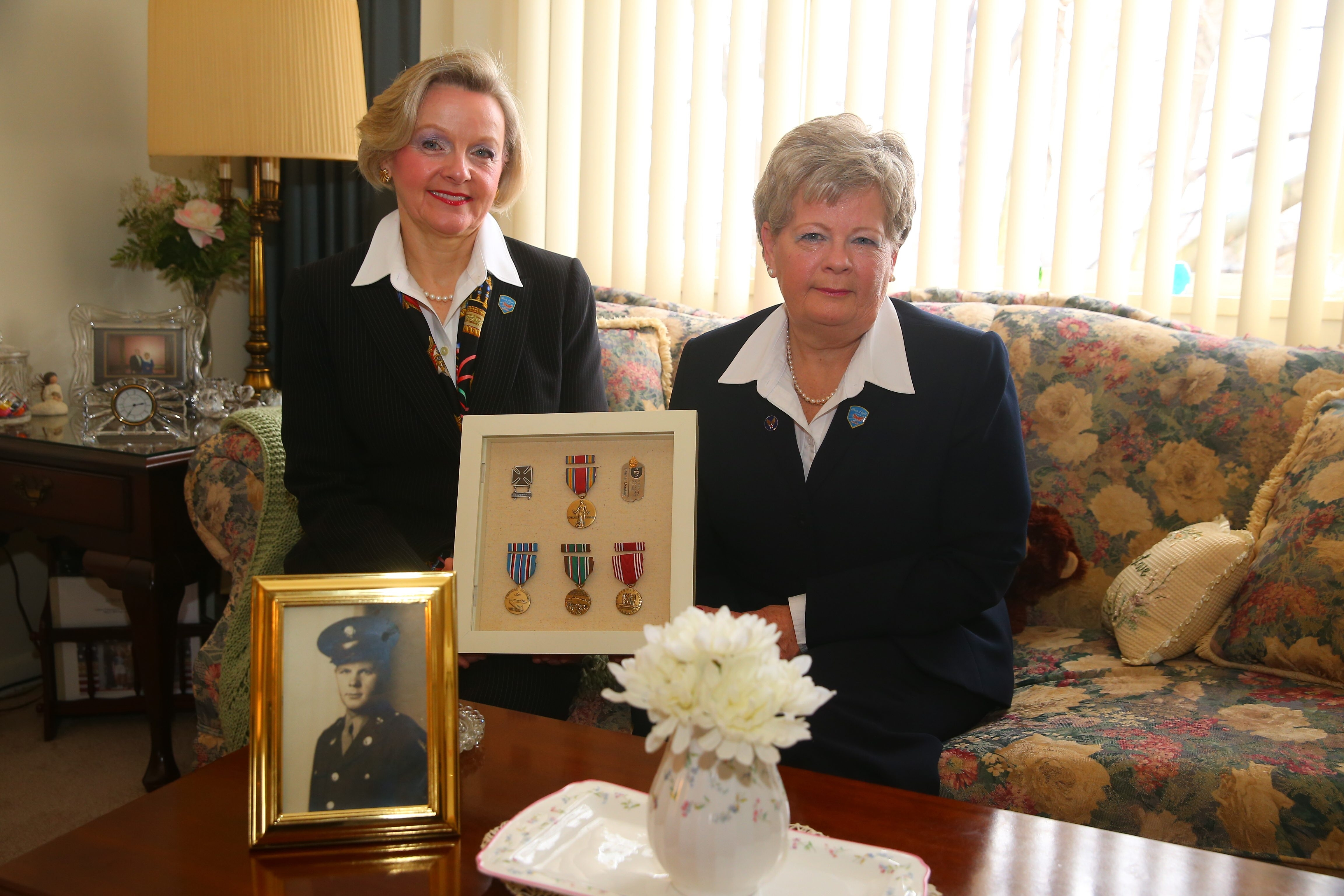 Jo-Anne Wylie, left, and her sister, Lisa, display a photo of their father, Robert P. Wylie, and the medals he earned in World War II. His service inspired their volunteer work.