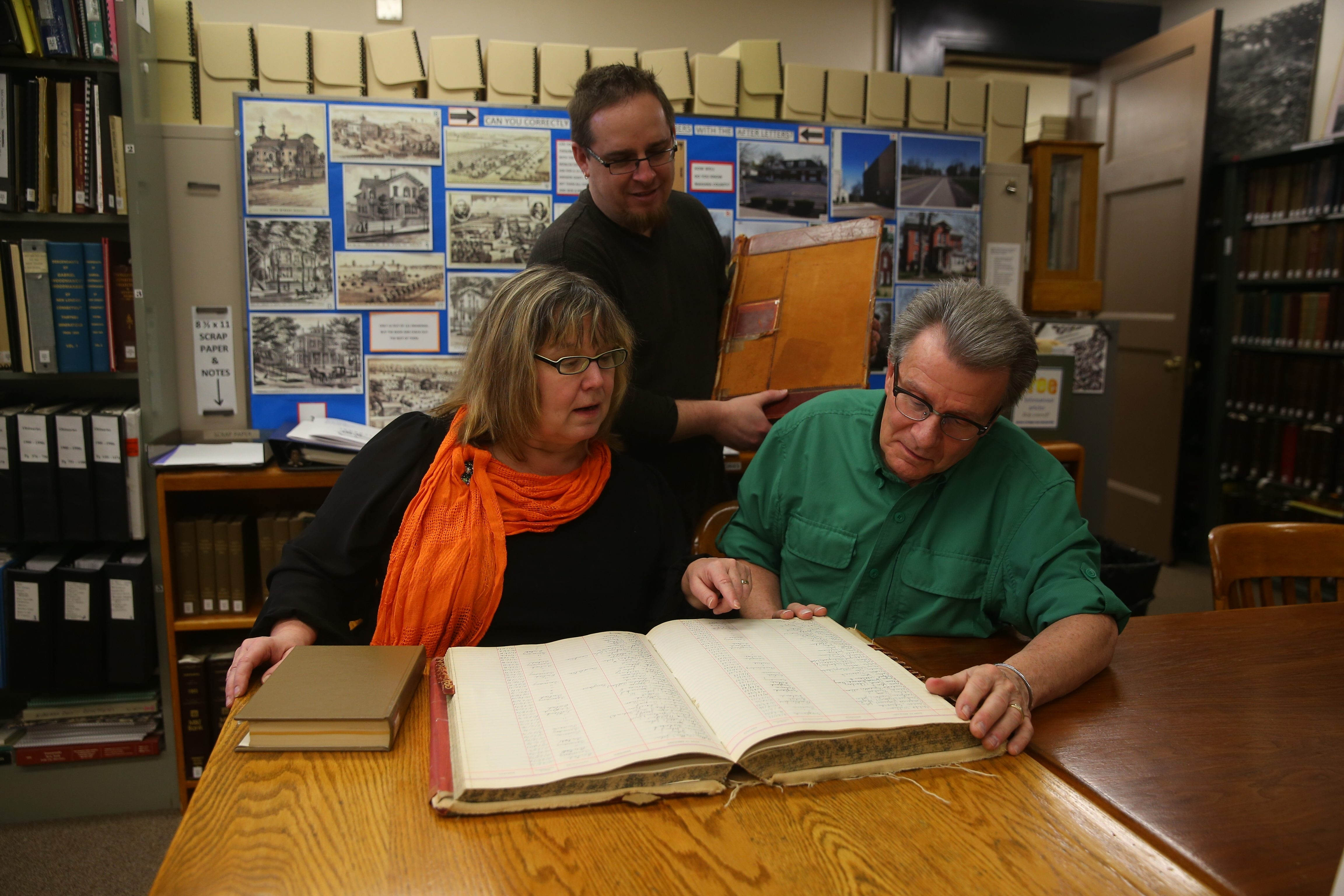 Catherine Emerson, left, historian, with deputies Ronald Cary, right and Craig Bacon, center peruse some of the genealogical resources available in the Niagara County Historian's Office, in the  Niagara County Clerk's Building in Lockport.