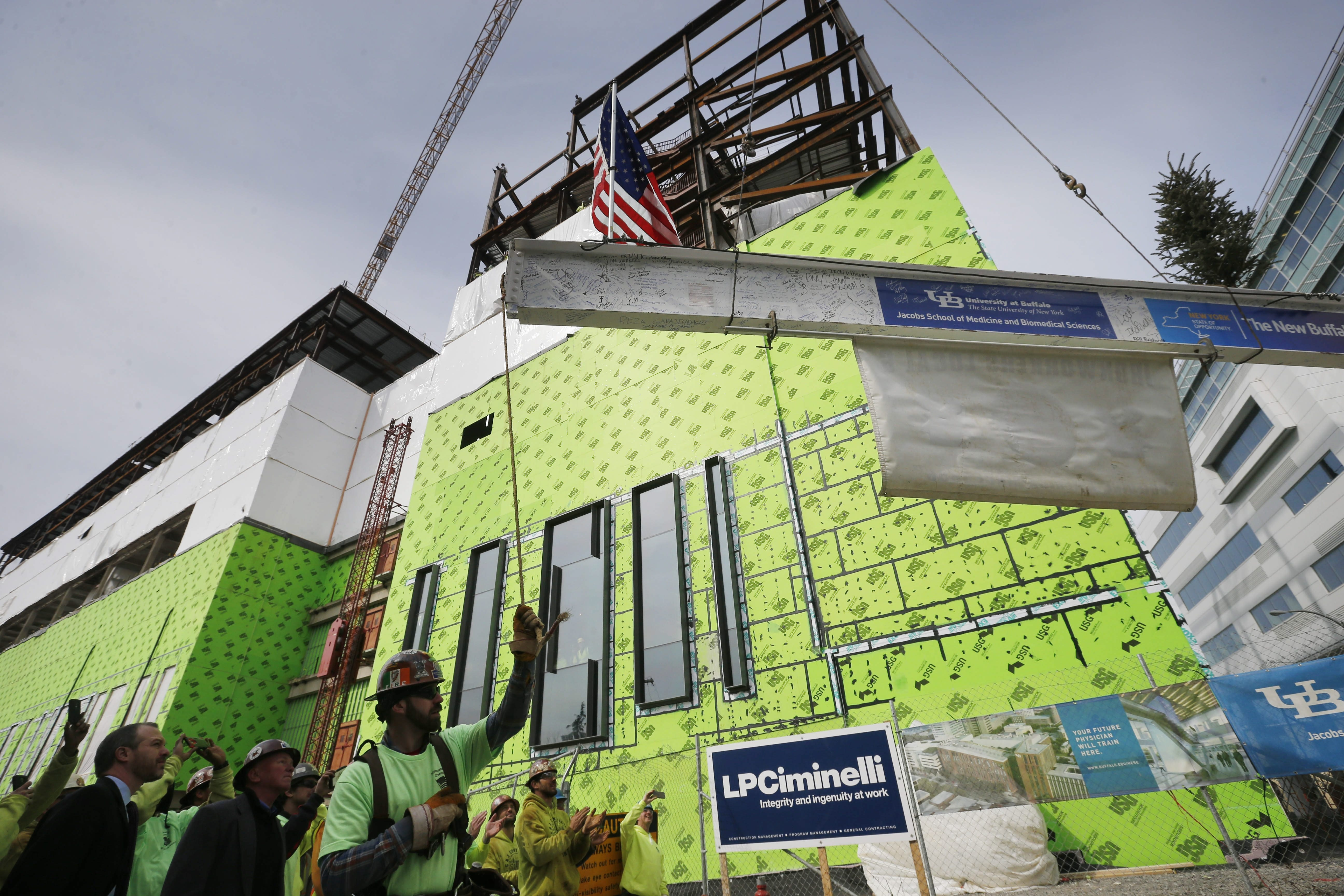"""The last beam is lifted into place Tuesday during a """"topping off"""" ceremony marking the completion of the frame of UB's new medical school."""