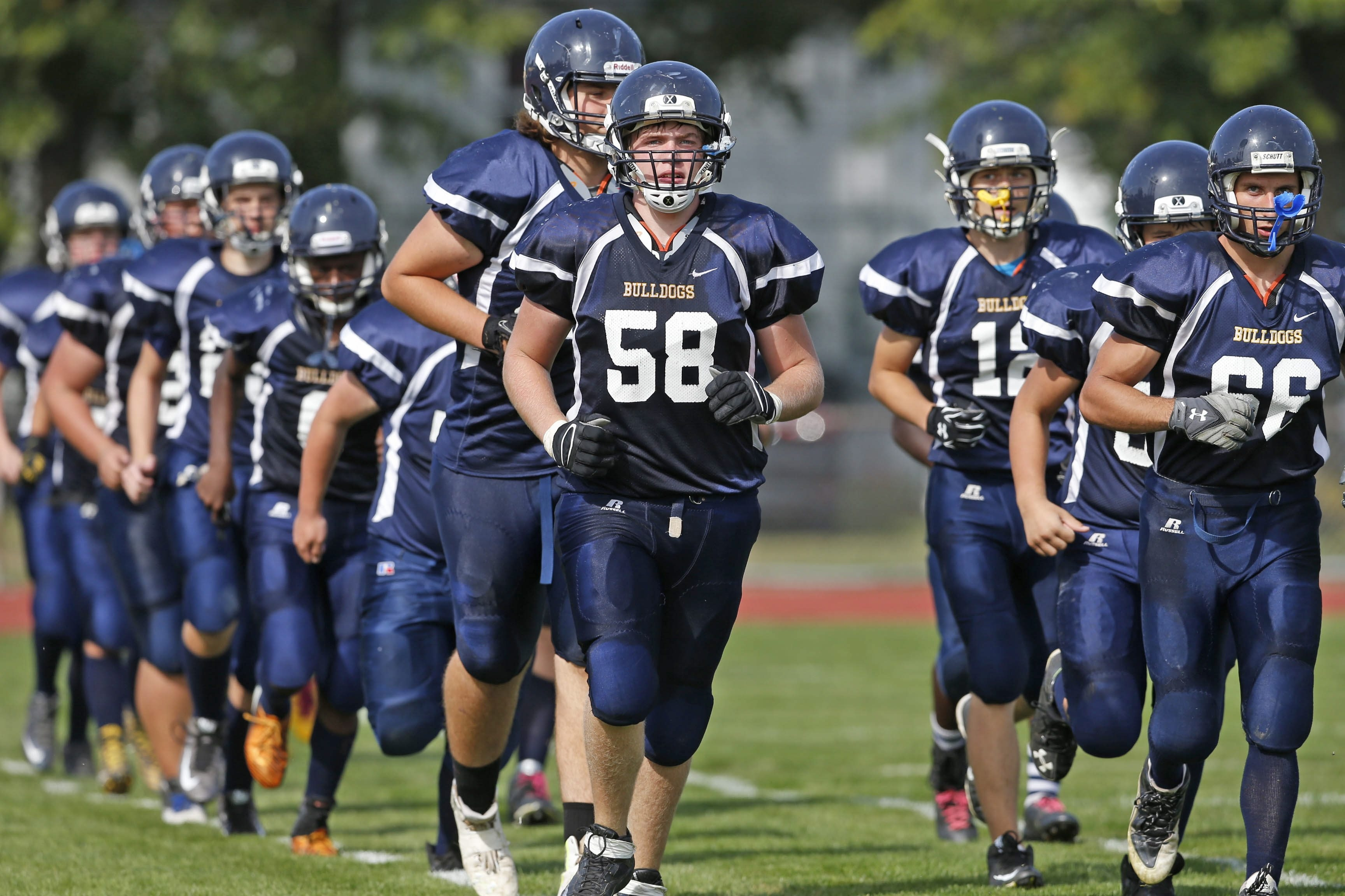 Kenmore Easts seniors Josh Moore (58) and Jacob Elgie (66) lead their team out on to the field to start the second half vs. Niagara Wheatfield at Kenmore East on Saturday, Sept. 26, 2015.  (Robert Kirkham/Buffalo News)