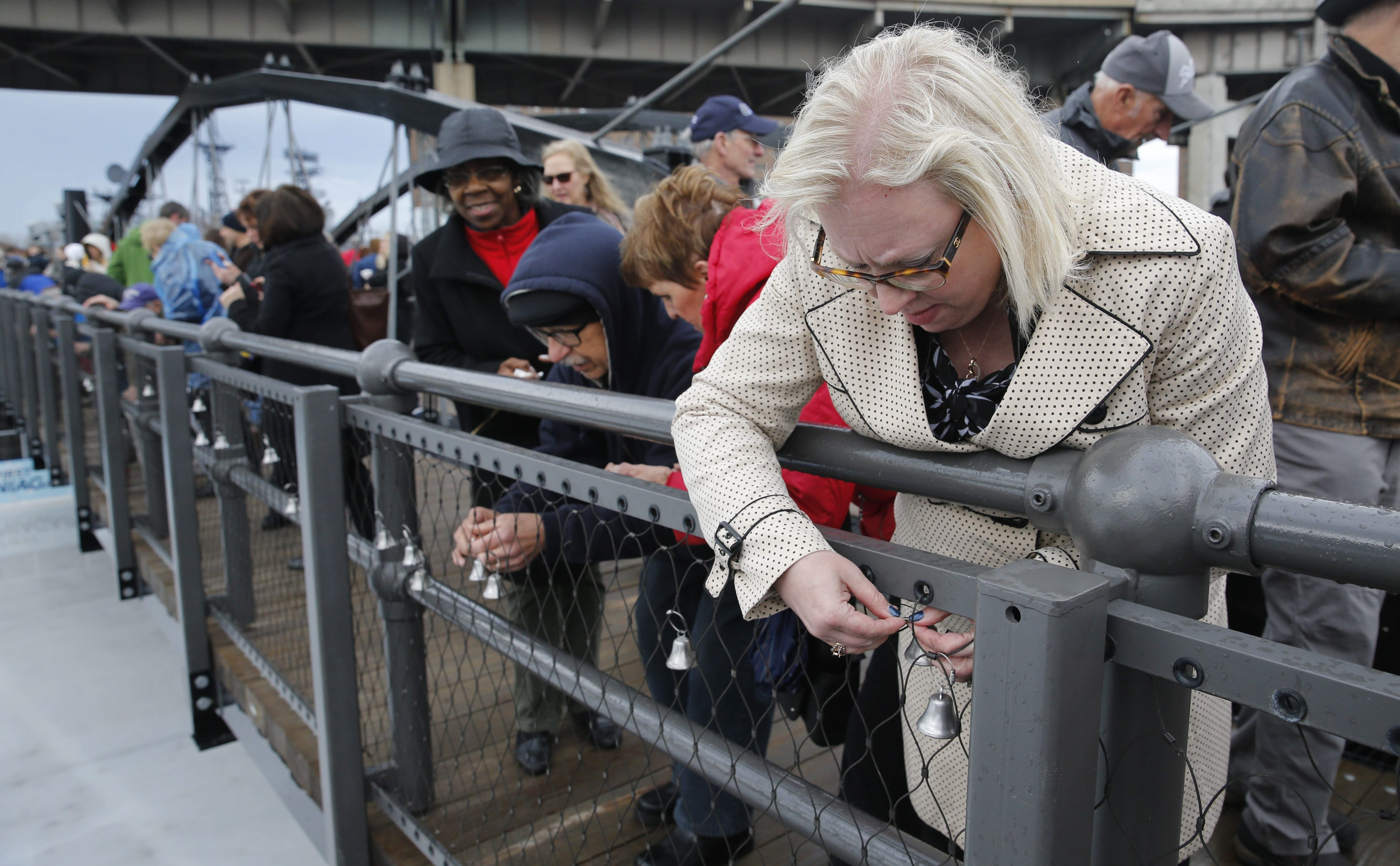 """Breast cancer survivor Rosanne Braxton of Snyder, right, with dozens of other survivors, hangs a bell on the  rededicated Roswell Park Cancer Institute """"Bridge of Hope"""" at Canalside."""