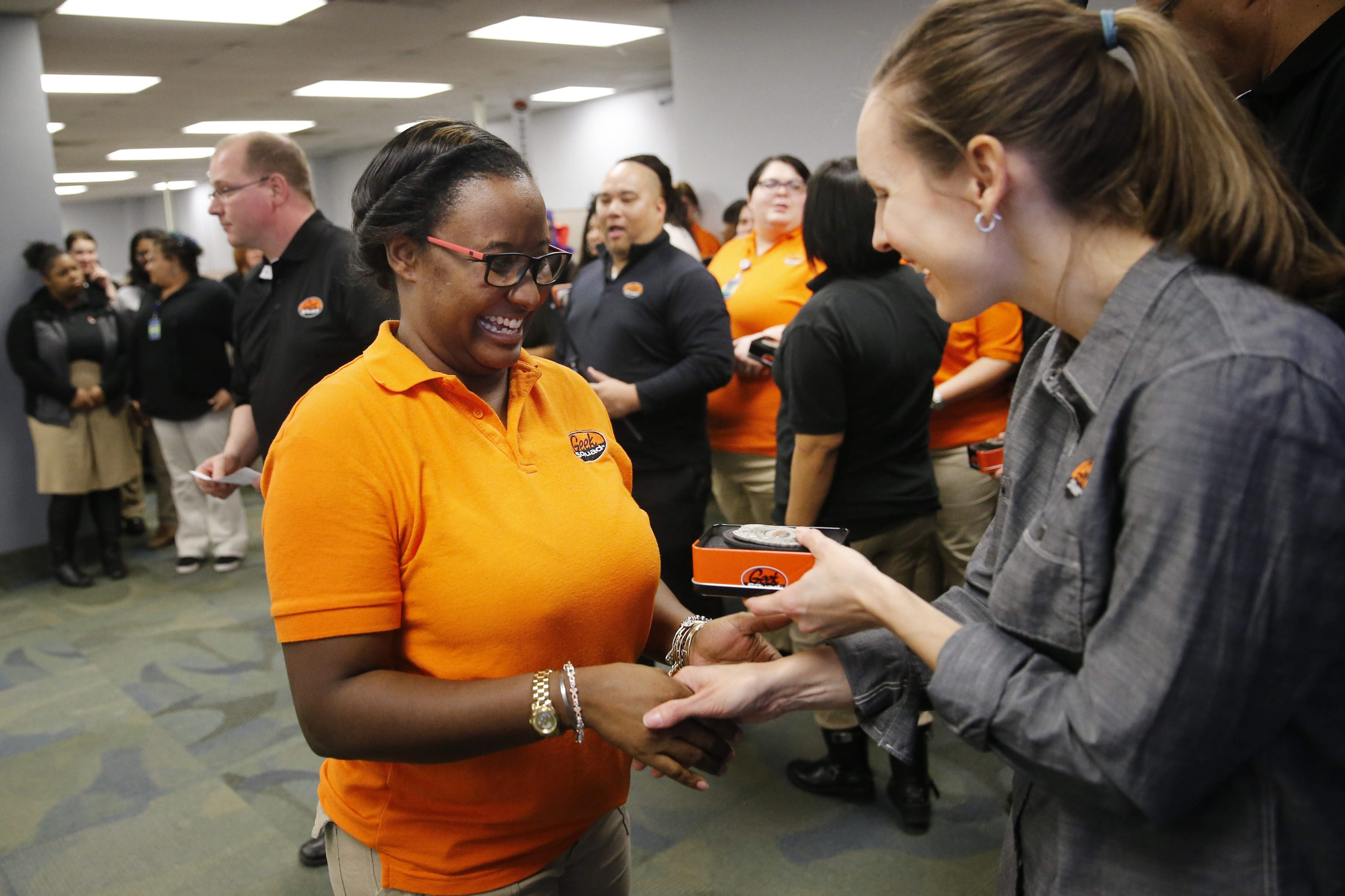INSTALLS Inc. customer service agent Candance Butler, left, receives her new Geek Squad badge from account manager Jen Hehir during a ceremony Wednesday.