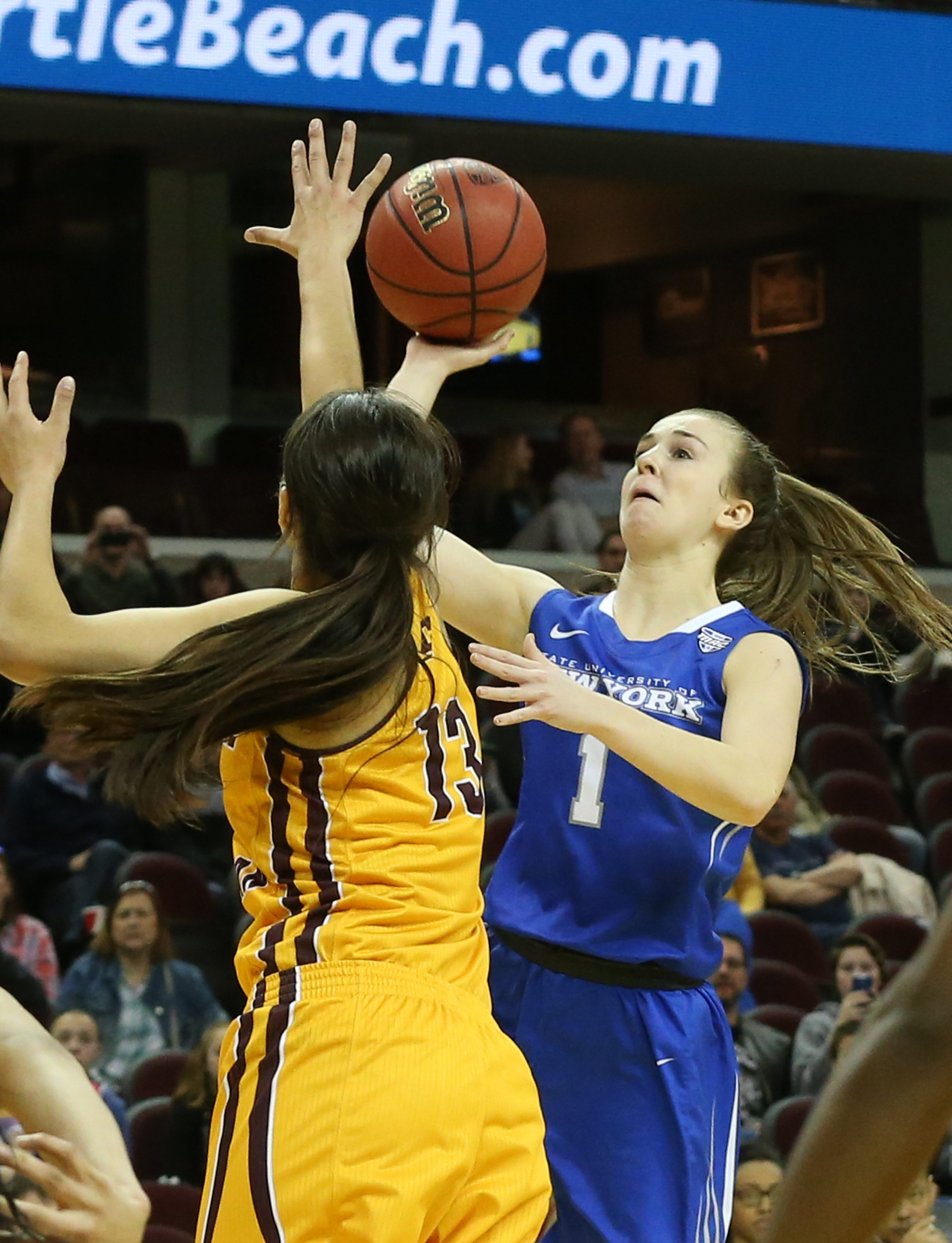 UB guard Stephanie Reid scores the game-winner over Central Michigan forward Reyna Frost in the MAC Championship game.