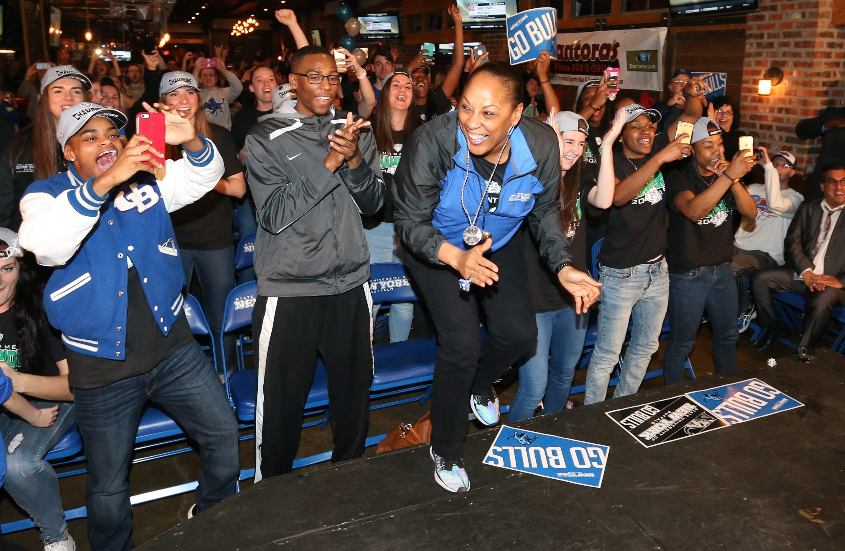 Buffalo Bulls Coach Felisha Legette-Jack and the women's basketball players react to their team being slated to play Ohio State while watching the NCAA basketball selection show at Santora's on Transit Road in Amherst on Monday, March 14, 2016.  (James P. McCoy/Buffalo News)