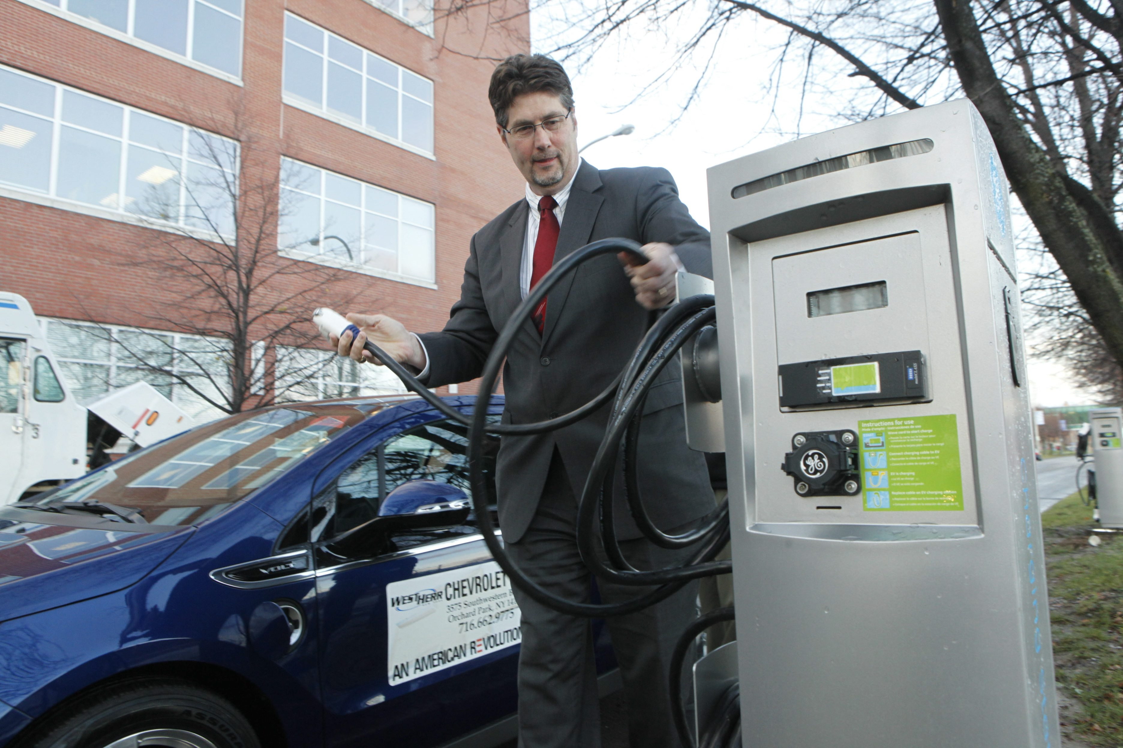 Dennis W. Elsenbeck, regional executive for National Grid, plugs in a Chevy Volt at one of the charging stations on the Buffalo Niagara Medical Campus.