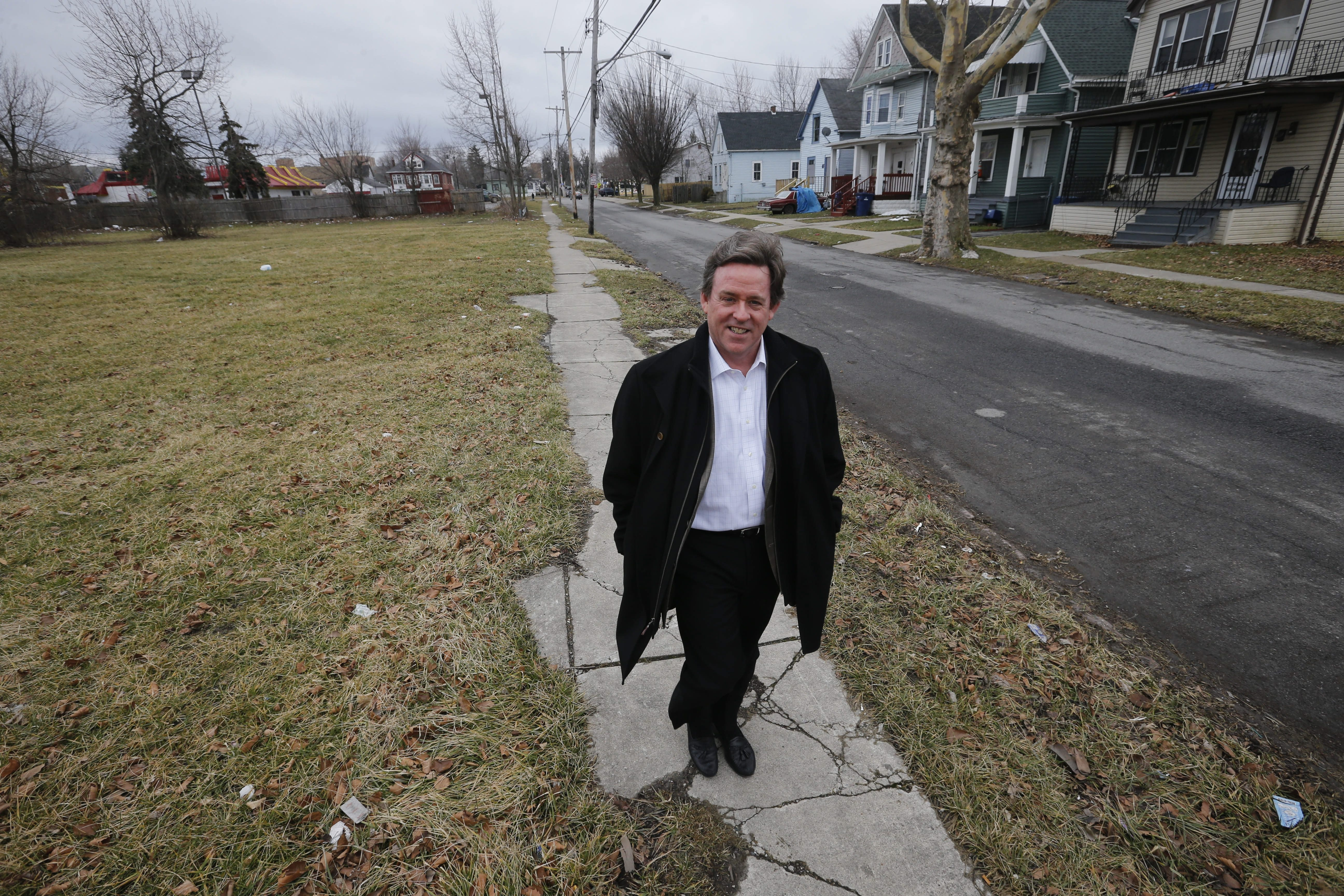 John Somers, owner of Harmac Medical Products, walks down Wende Street, where his company is planning to develop empty lots in an effort to help fix up the neighborhood around the company's Bailey Avenue plant. (Derek Gee/Buffalo News)