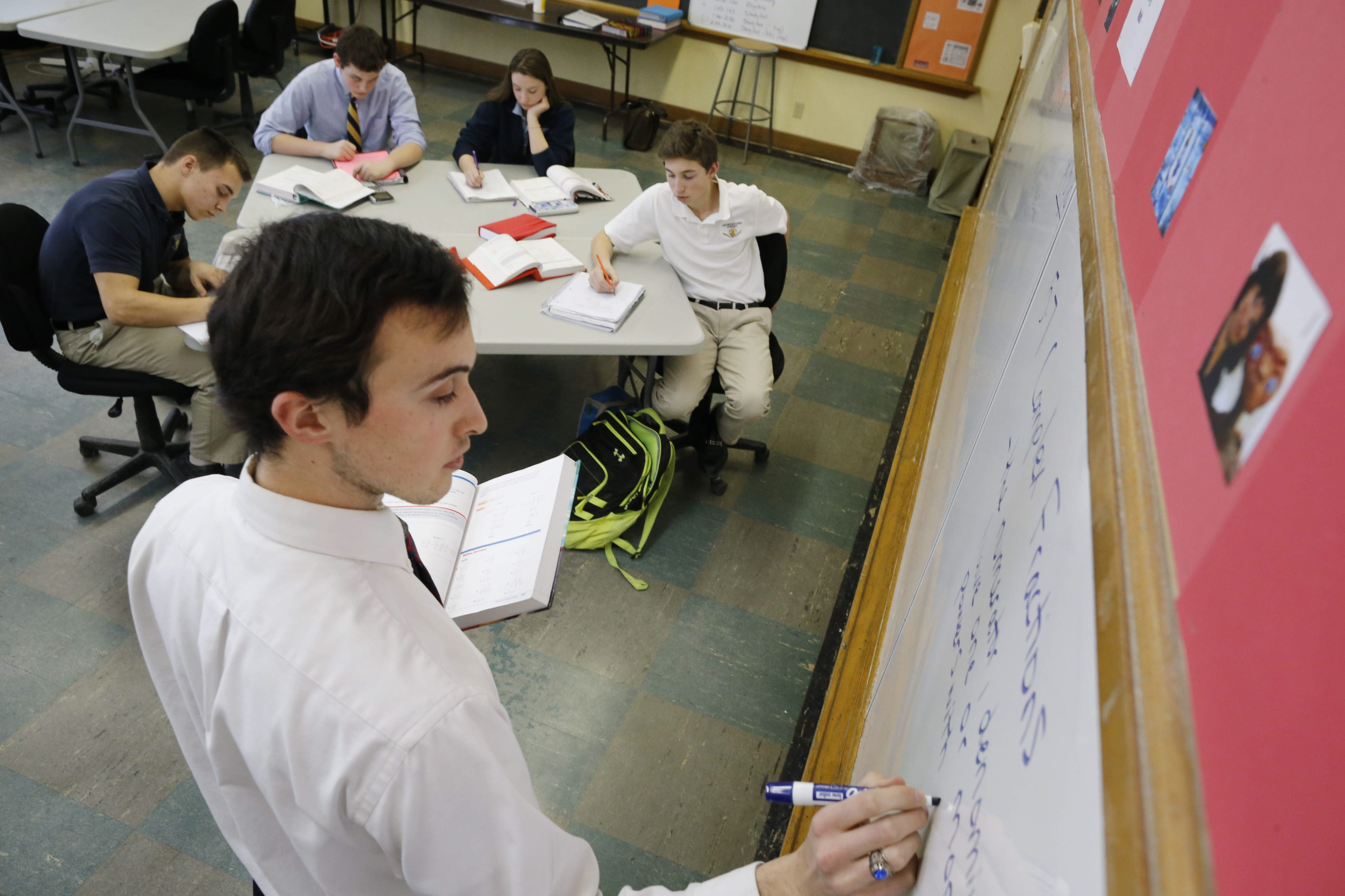 Andrew Suchyna teaches trigonometry to a class of four at the Chesterton Academy of Buffalo, located in a building that previously housed a Catholic school in West Seneca. The normal class size is seven.