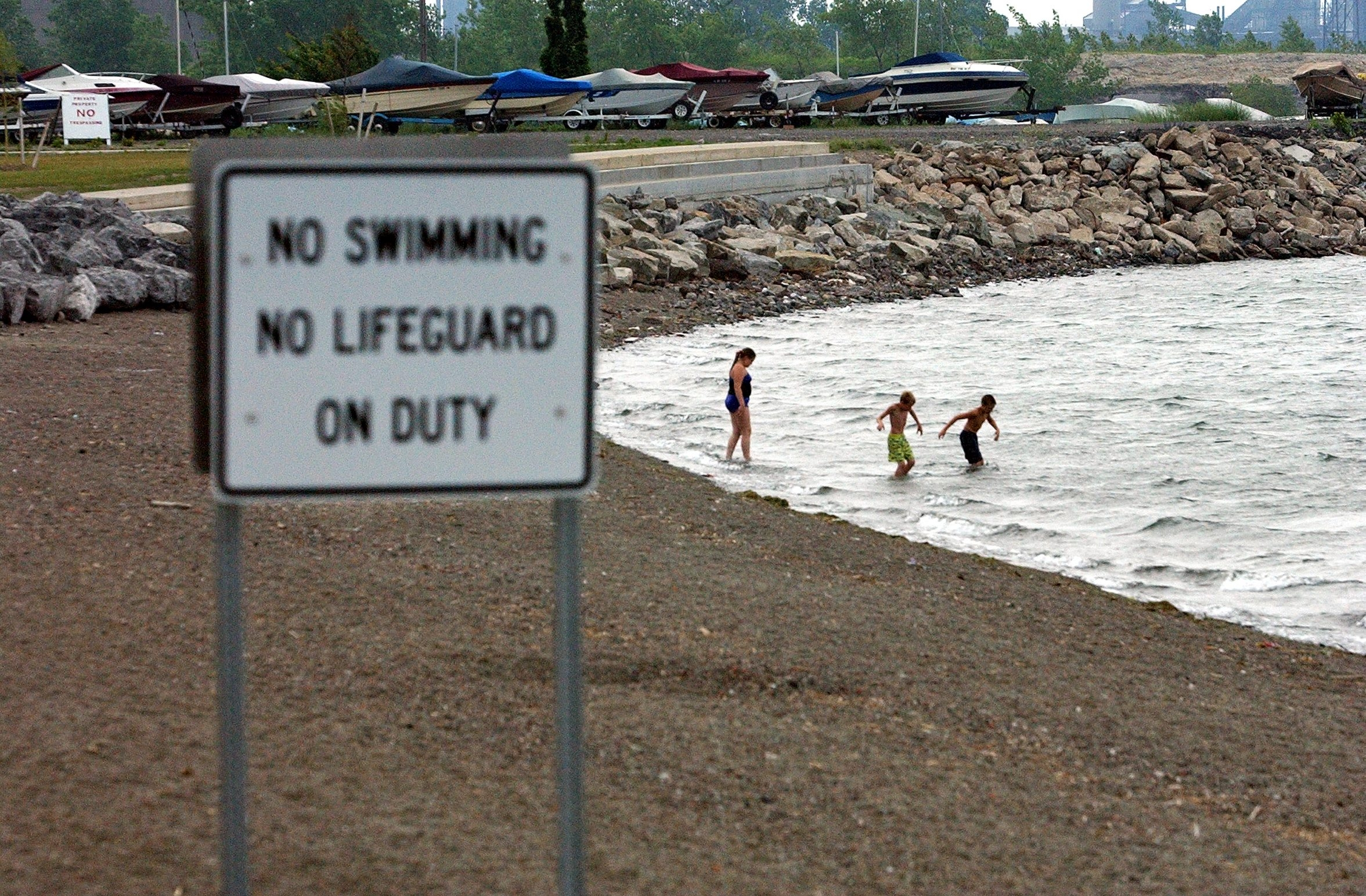 "A file photo shows children ignoring the ""no swimming"" sign at Gallagher Beach. The state says the cost of maintaining a sand beach and the likelihood the beach would frequently close over water safety issues make swimming unsuitable there."