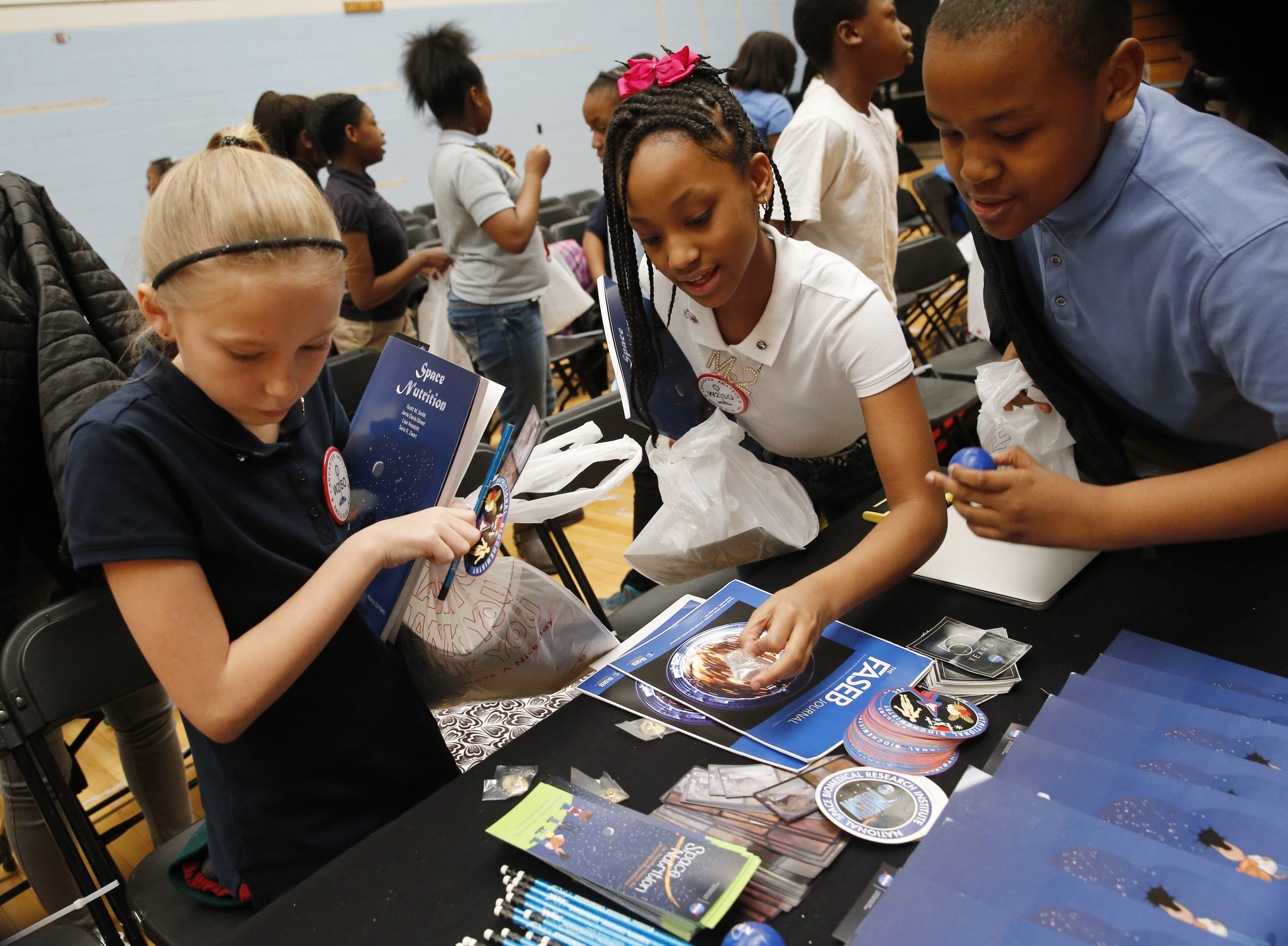 Harvey Austin students, from left, Denise Yerry, Eloni Herndon and Elijah Mostiller pick up some information about life in space after their class had a space chat with astronaut Tim Copra aboard the International Space Station on Tuesday.